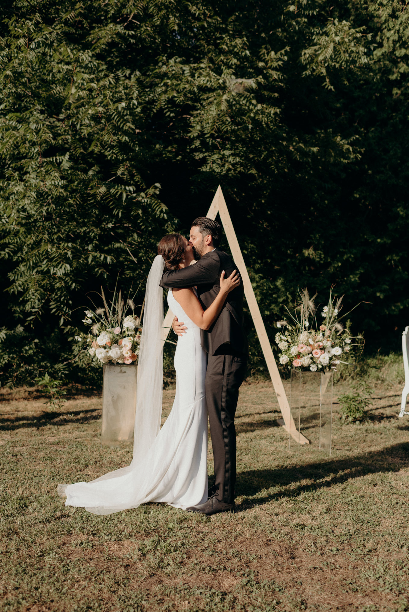 bride and groom first kiss surrounded by trees