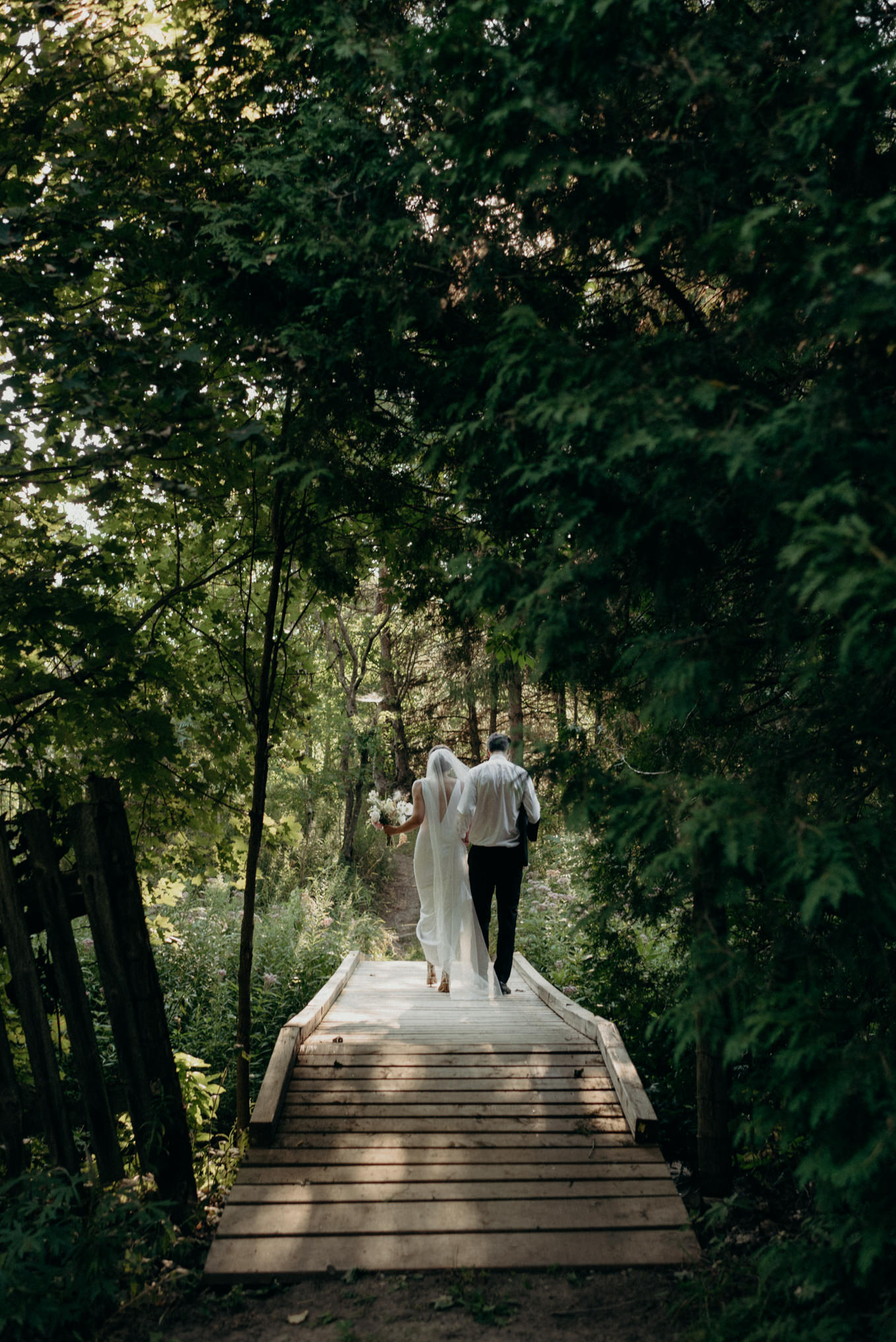 bride and groom walking in nature forest on wedding day