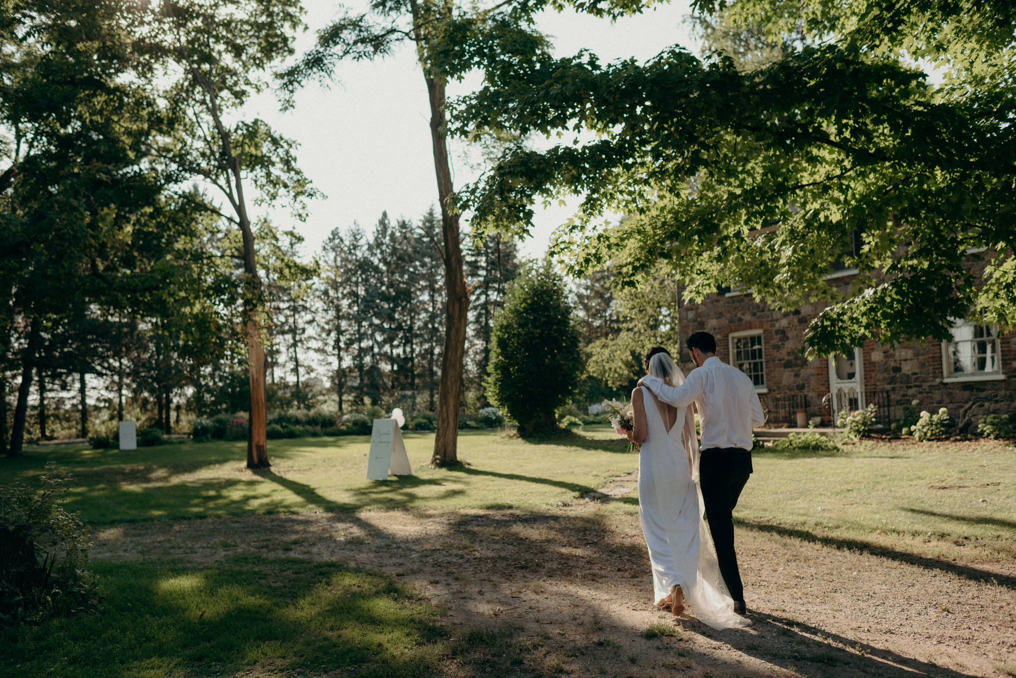 bride and groom walking on treed farm property after ceremony