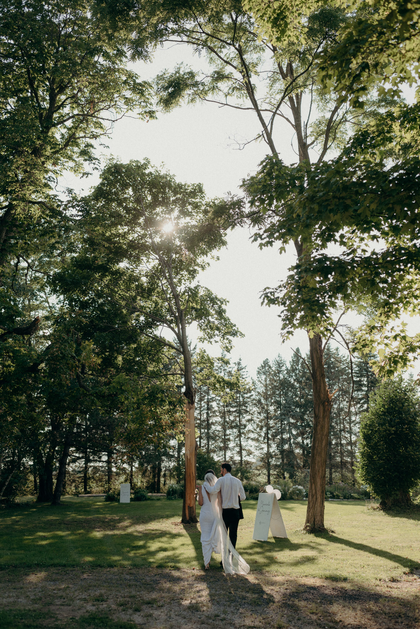 bride and groom walking under tall trees in front of farm house