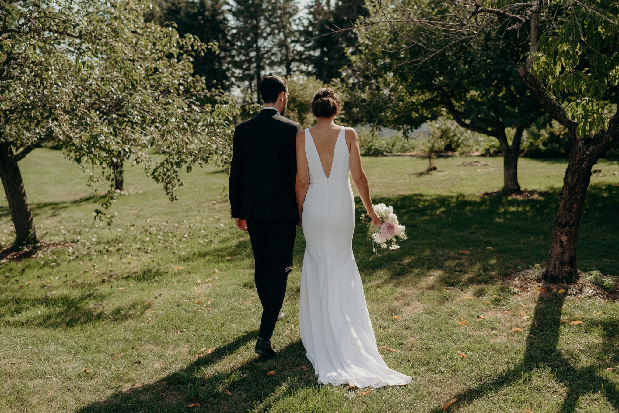 bride and groom walking on grass between trees