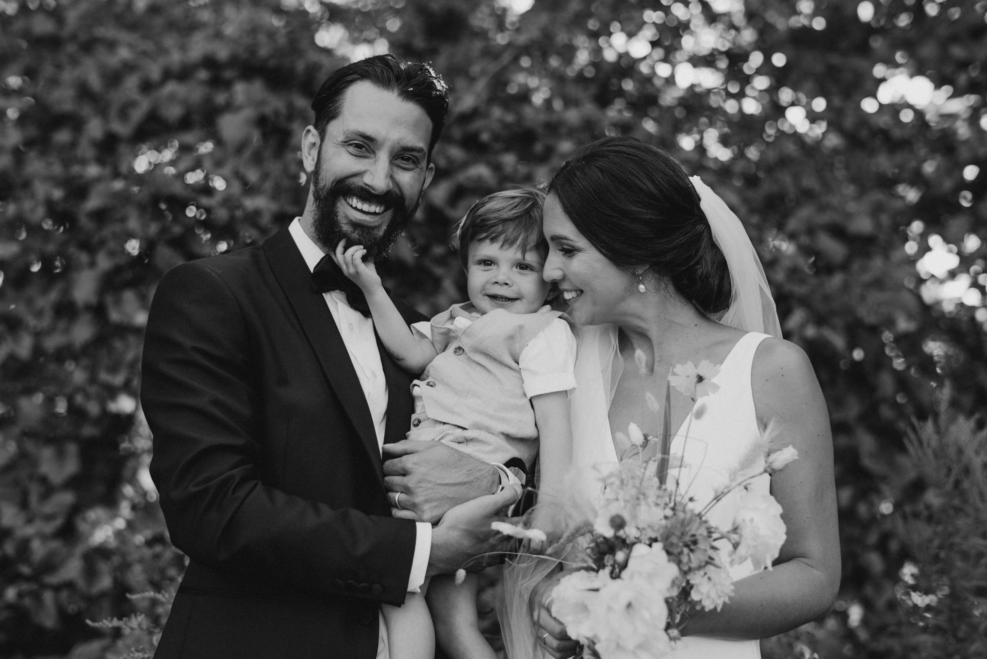 bride and groom posing with nephew