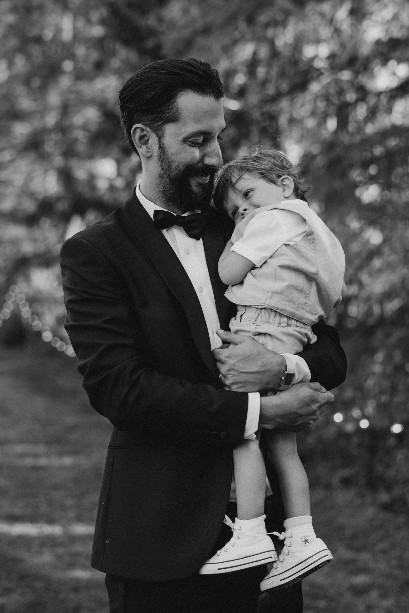 groom carrying adorable toddler nephew