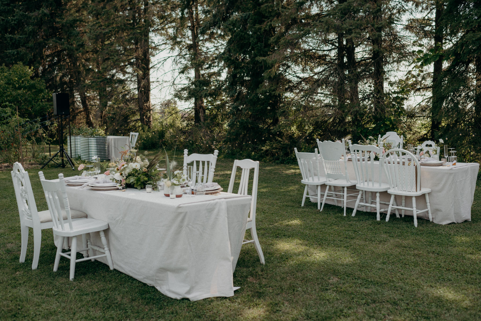 tables with white linens and chairs set up on grass garden for outdoor wedding