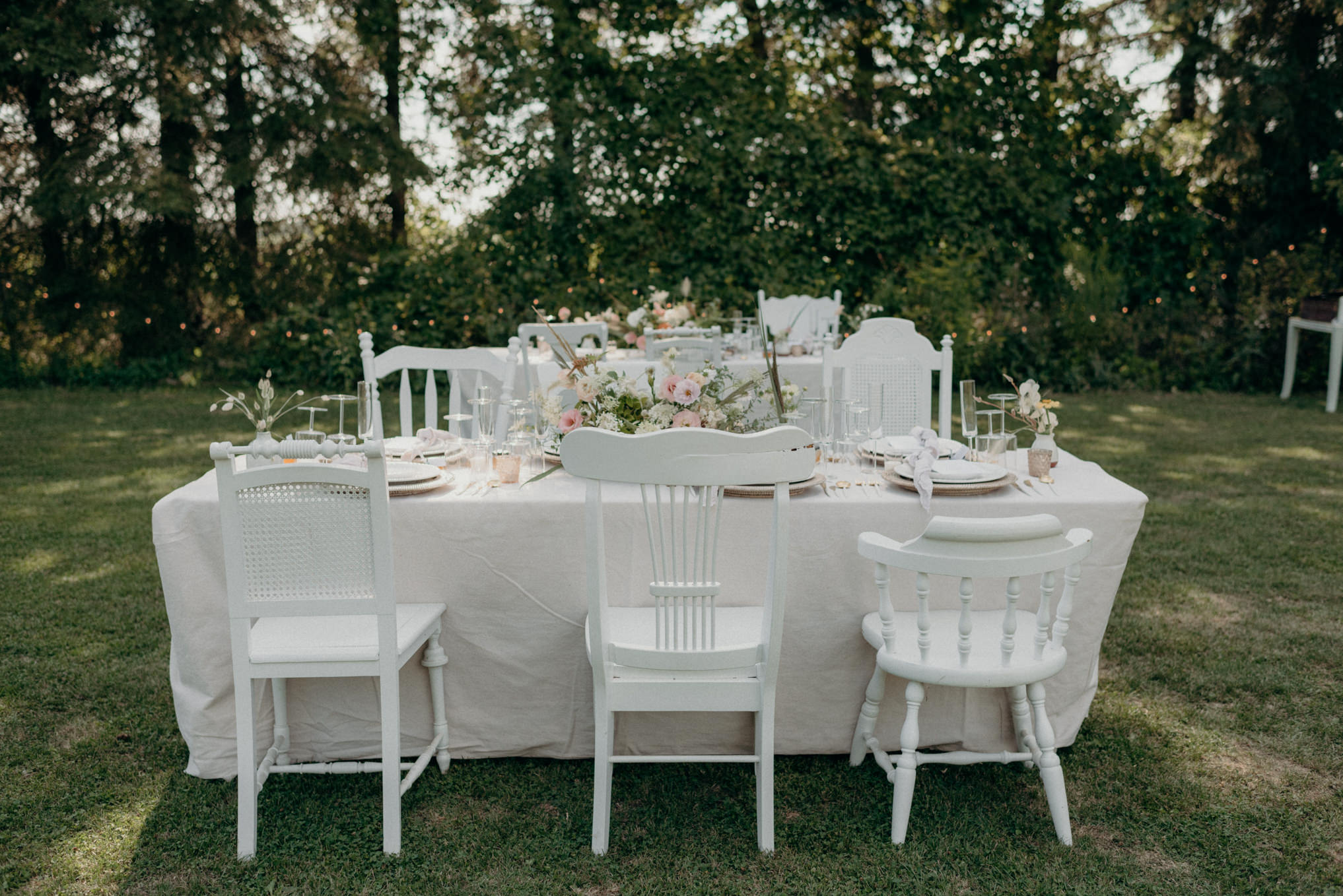 tables set up for outdoor wedding reception on grass surrounded by trees and string lights