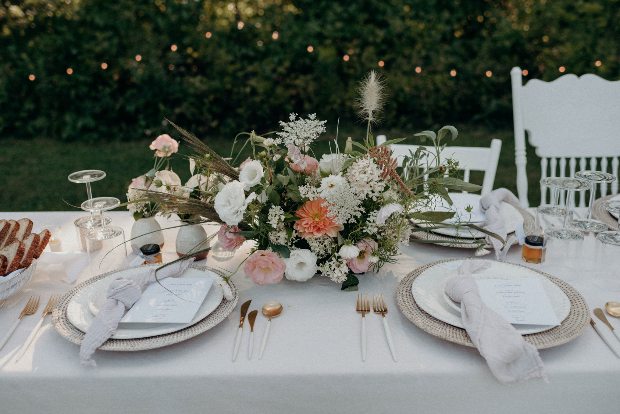 outdoor wedding reception table setting with flower centre piece and string lights