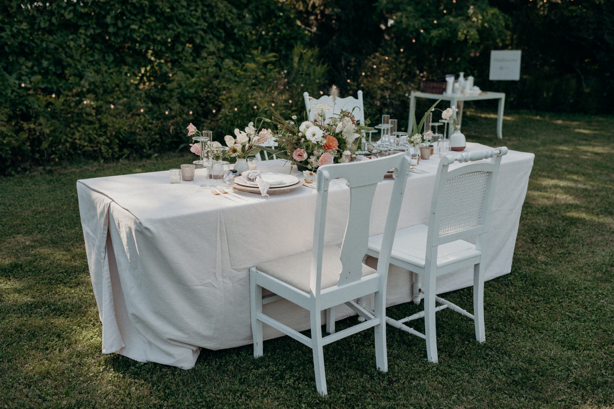 outdoor wedding reception on grass, table setting with string lights on trees