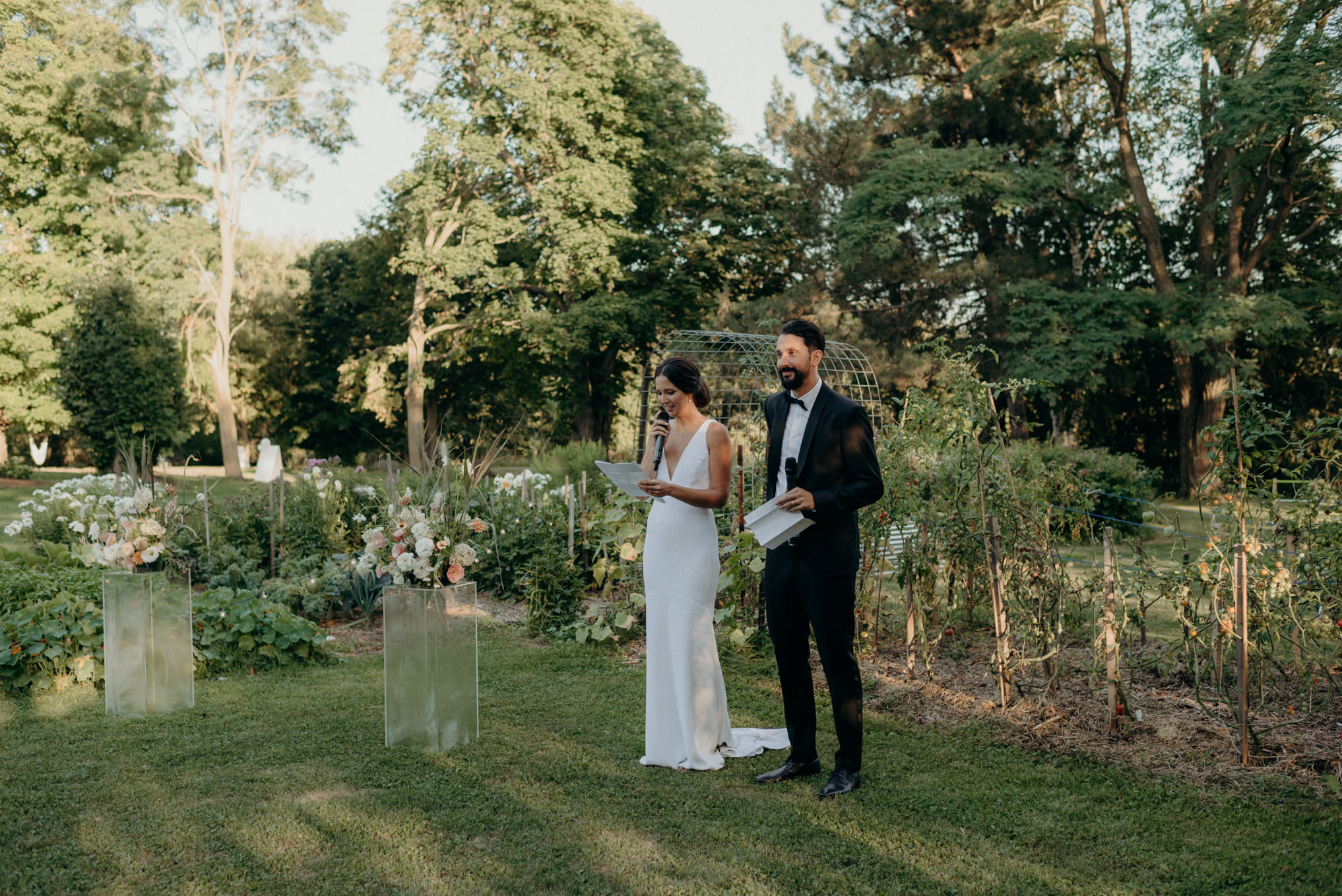 bride and groom saying speech on grass surrounded by garden and trees