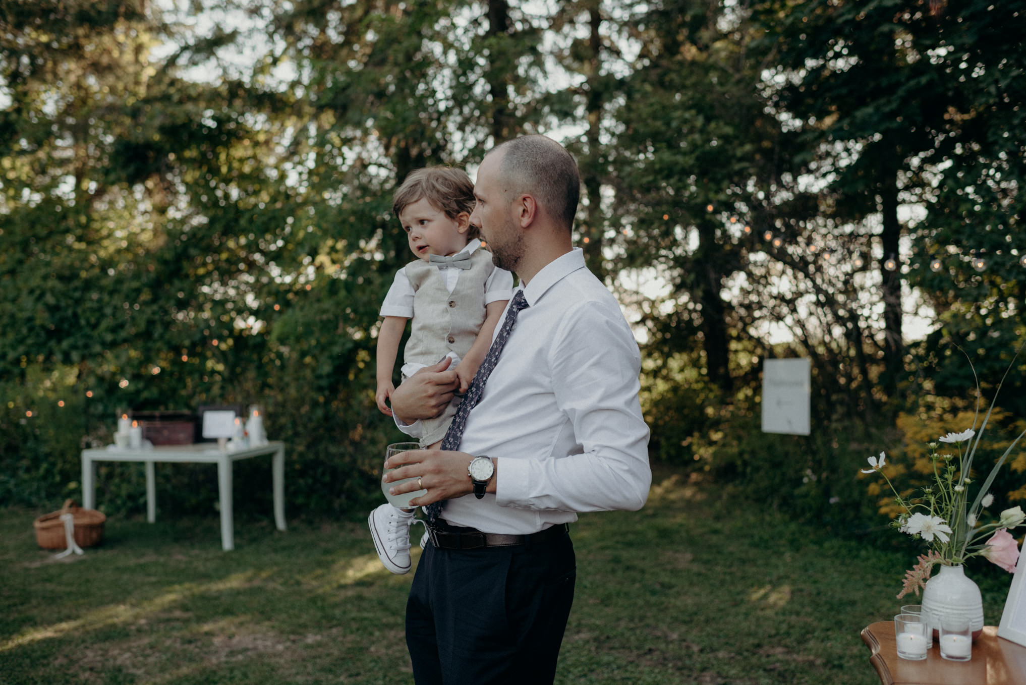father carrying toddler son at wedding reception outside