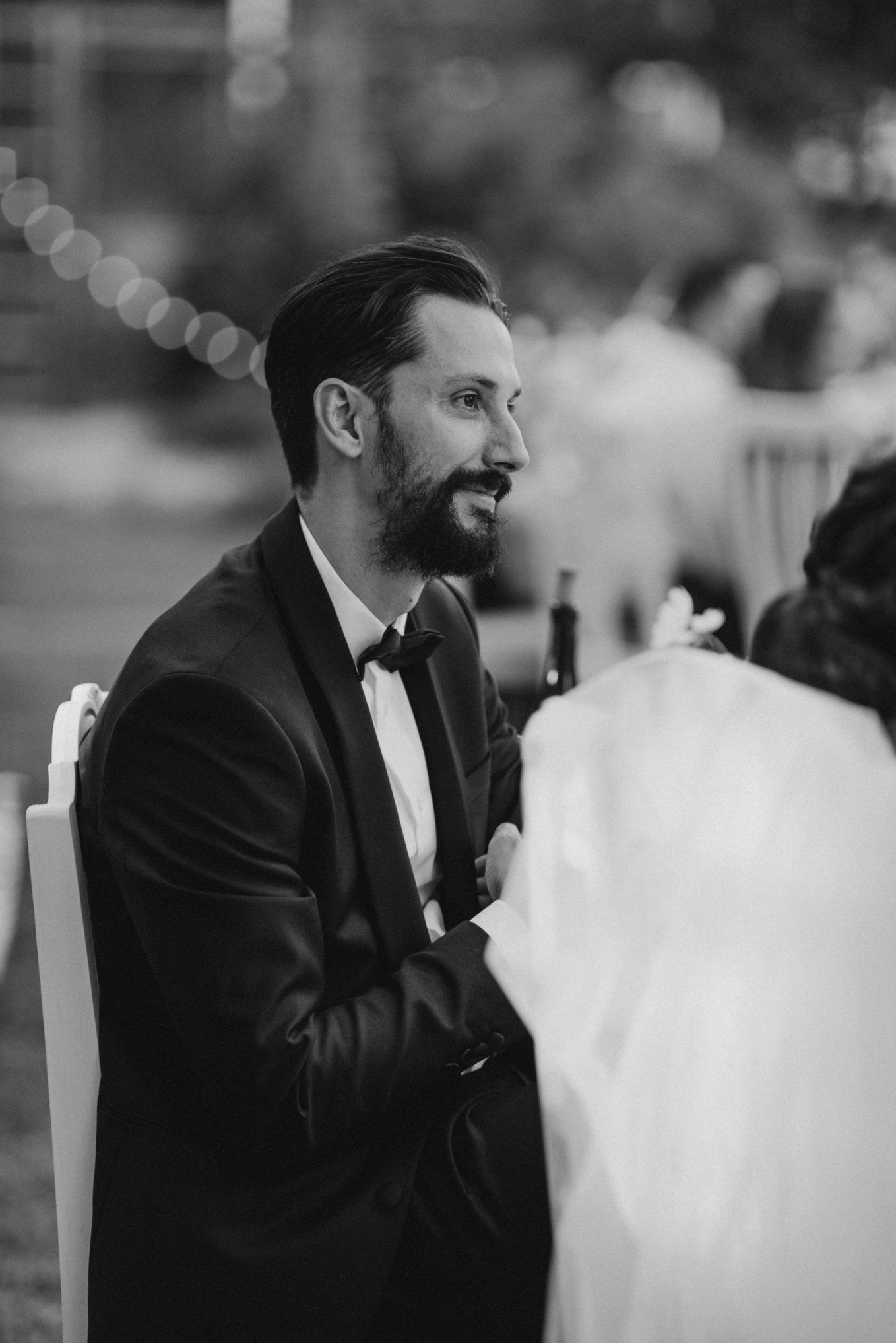 groom listening to speeches at wedding