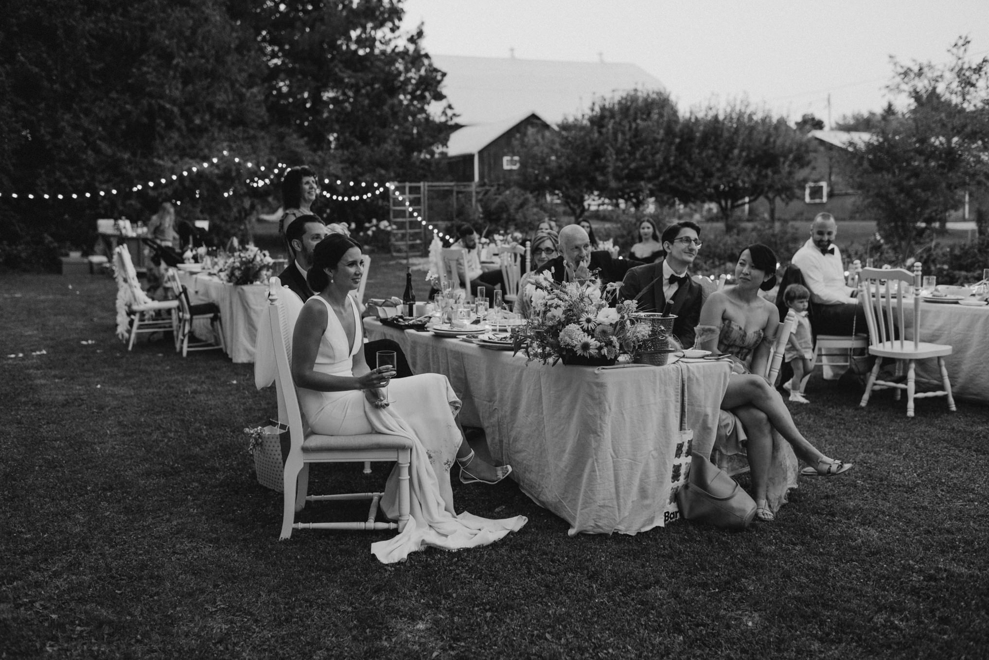 guests listening to speeches at wedding, black and white