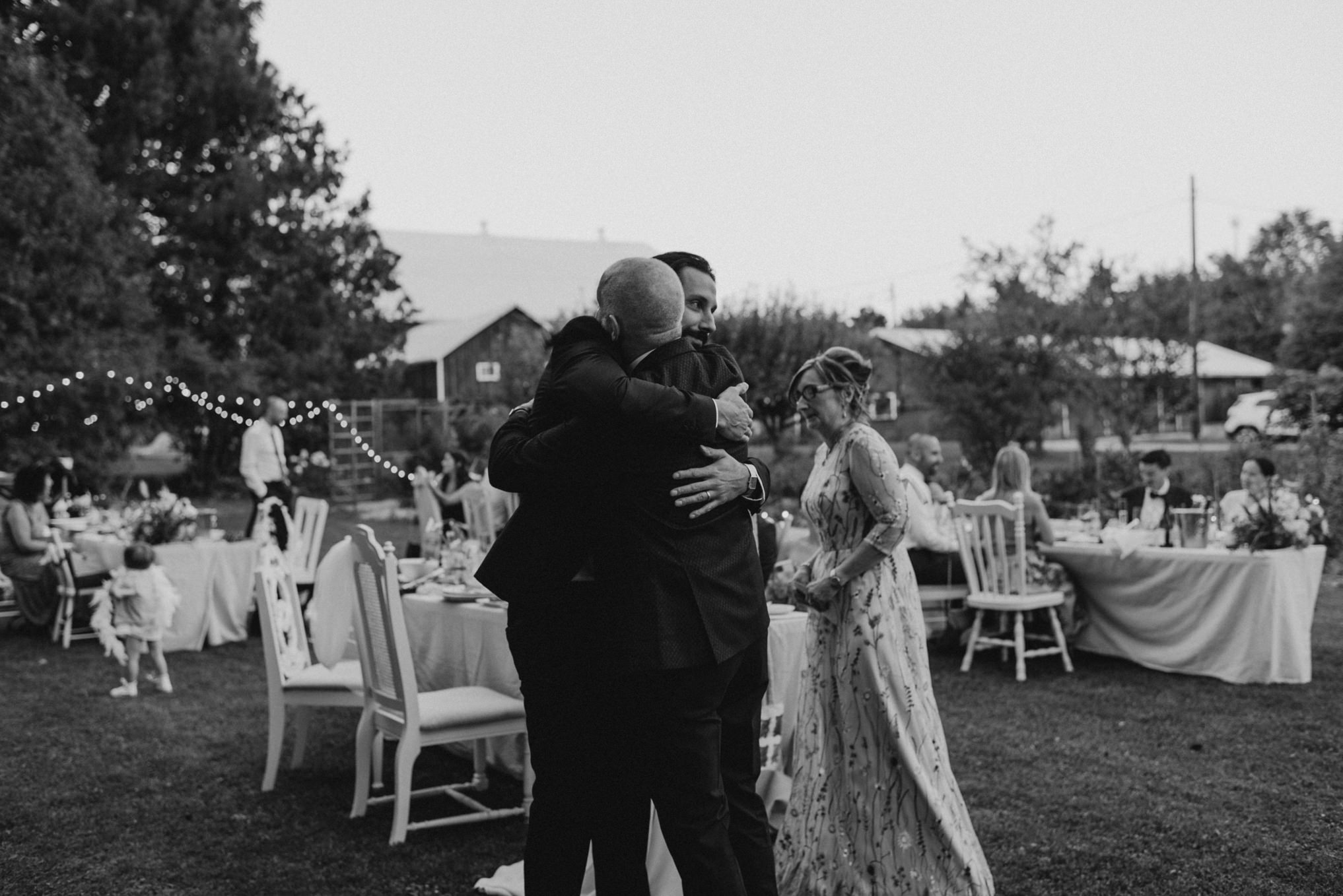 groom hugging father at wedding, black and white