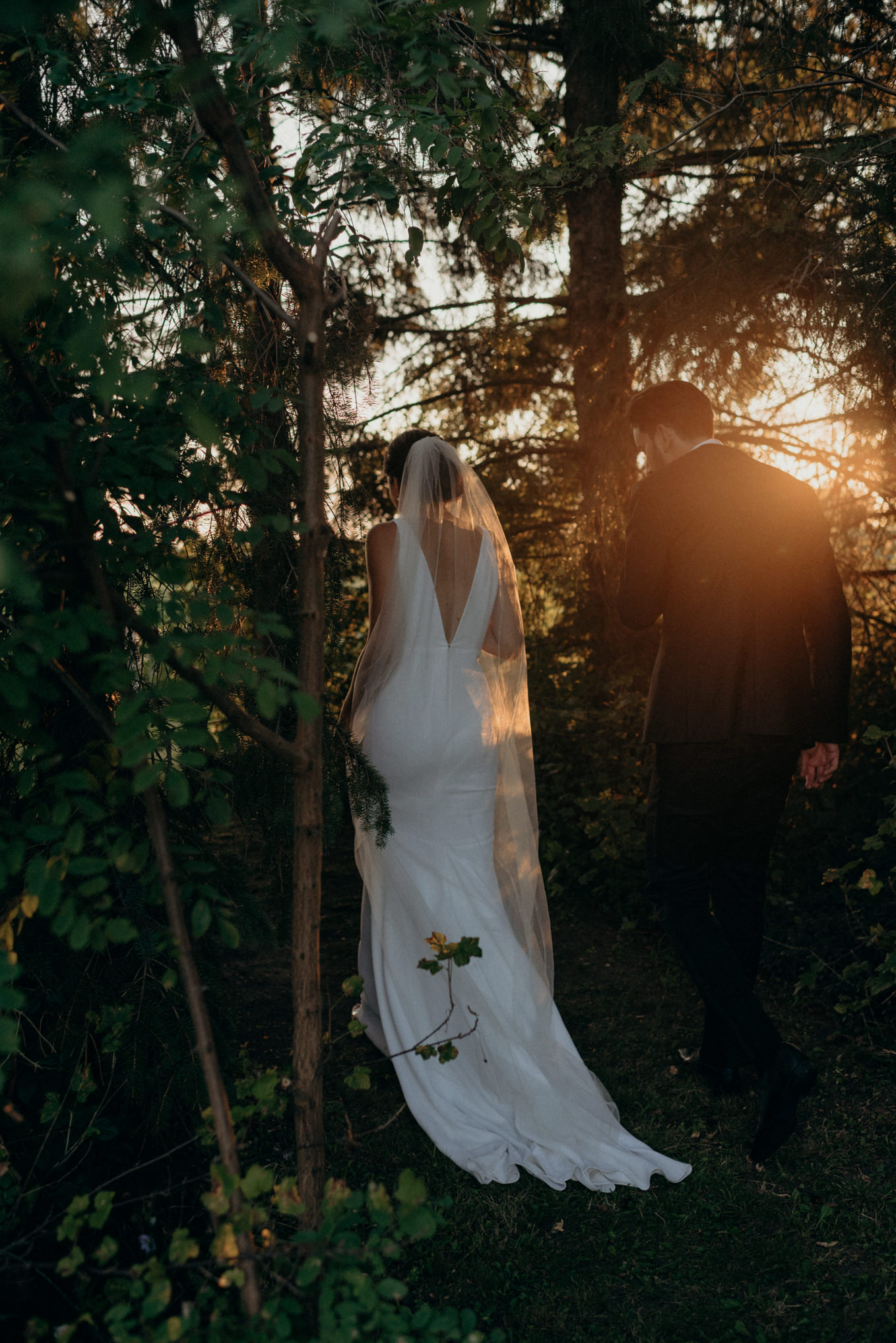 bride and groom walking into forest at sunset