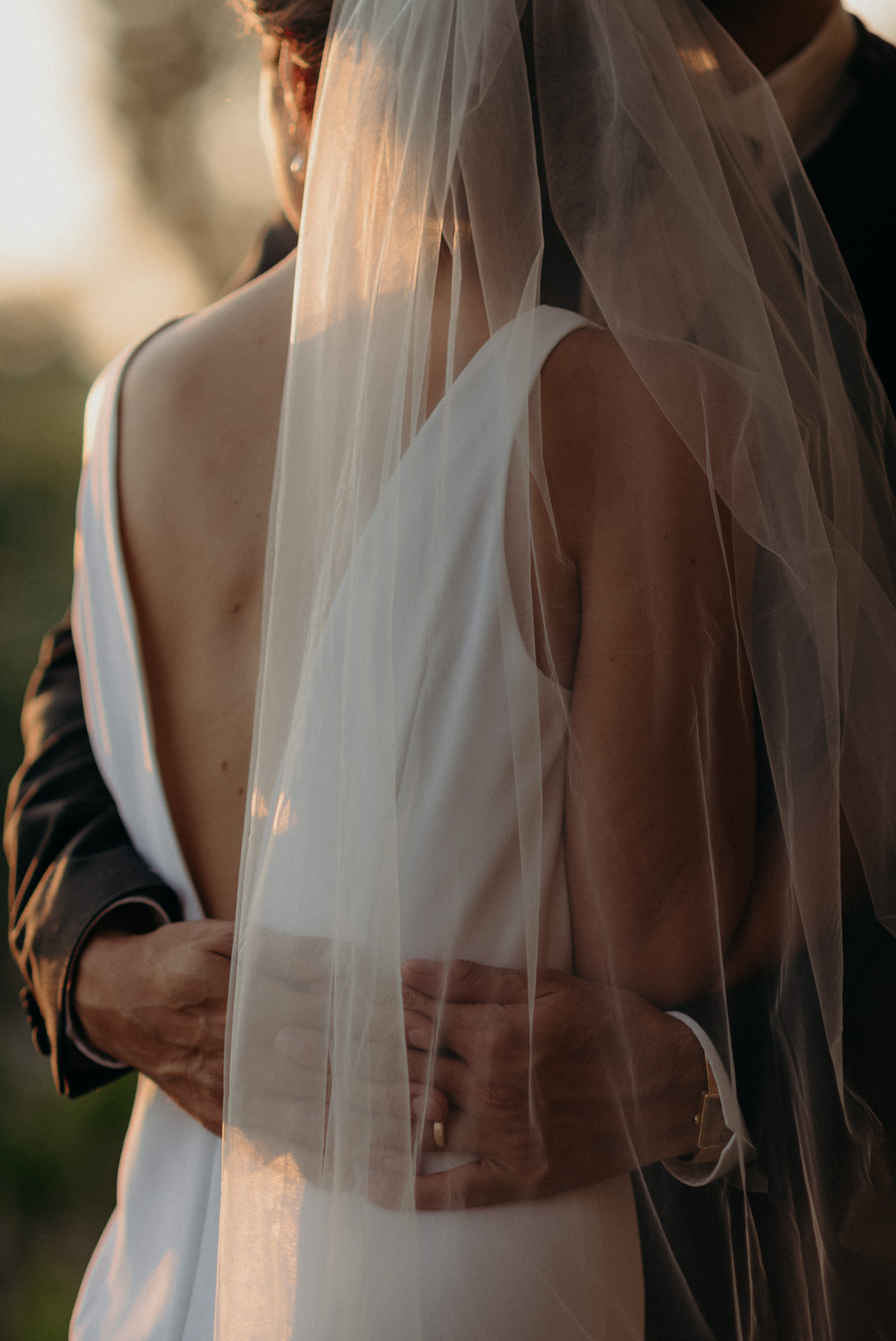 closeup of grooms hands on brides waist as they watch the sun set over a corn field