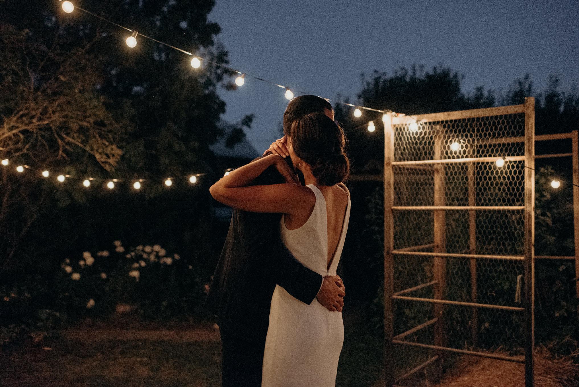 Bride and groom dancing under string lights outside