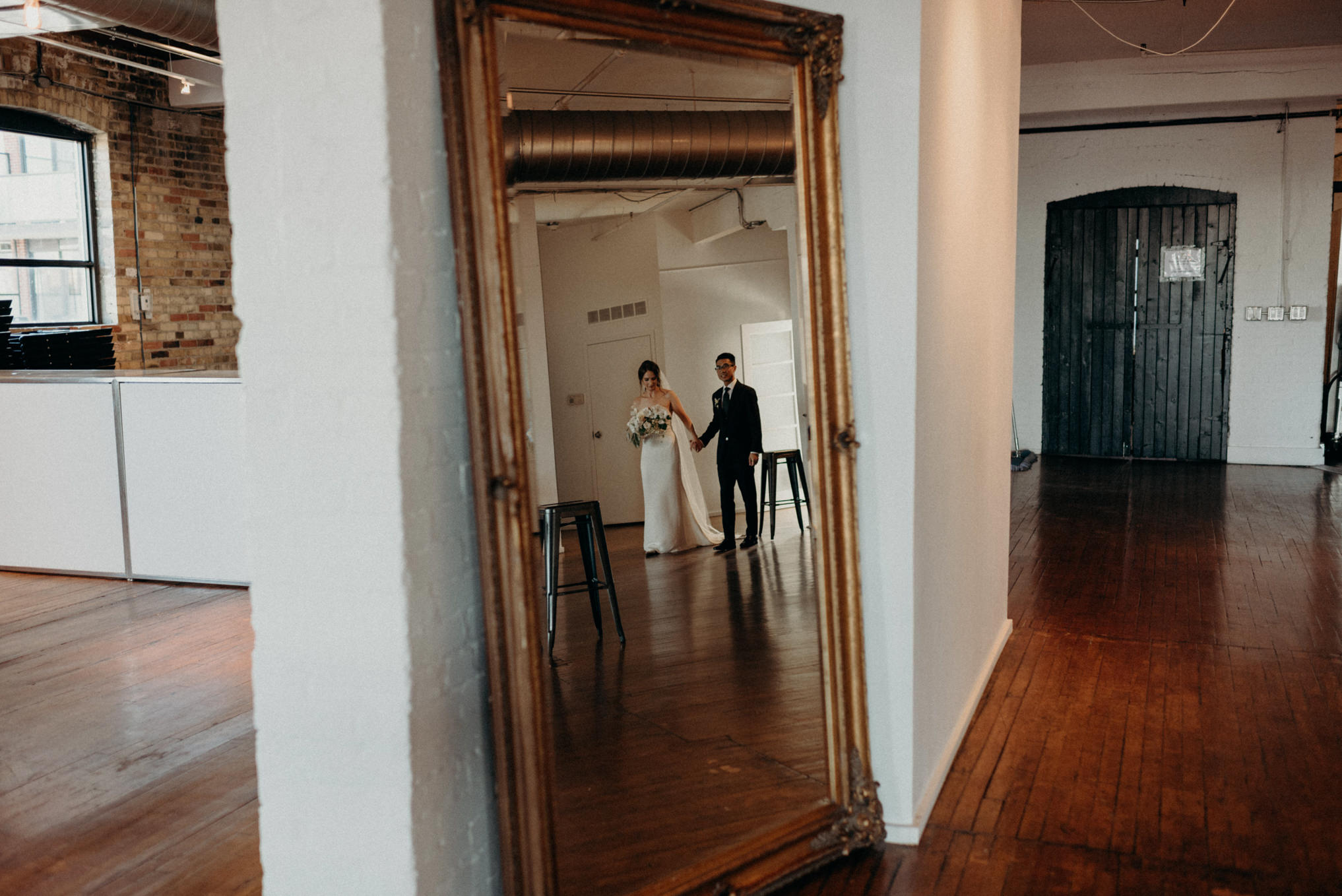 reflection of bride and groom in mirror holding hands and walking inside old loft