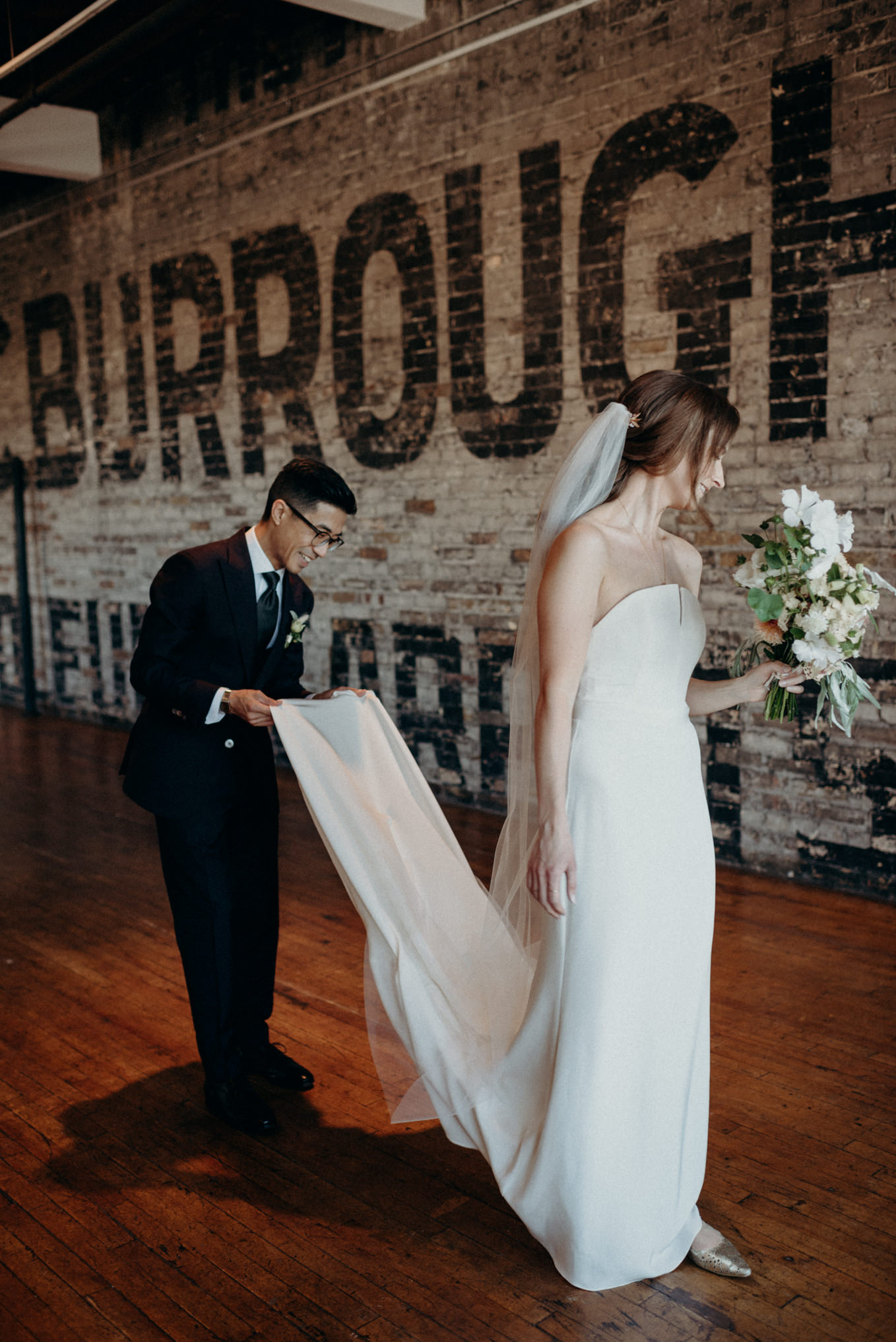 groom fixing bride's dress at The Burroughes elopement