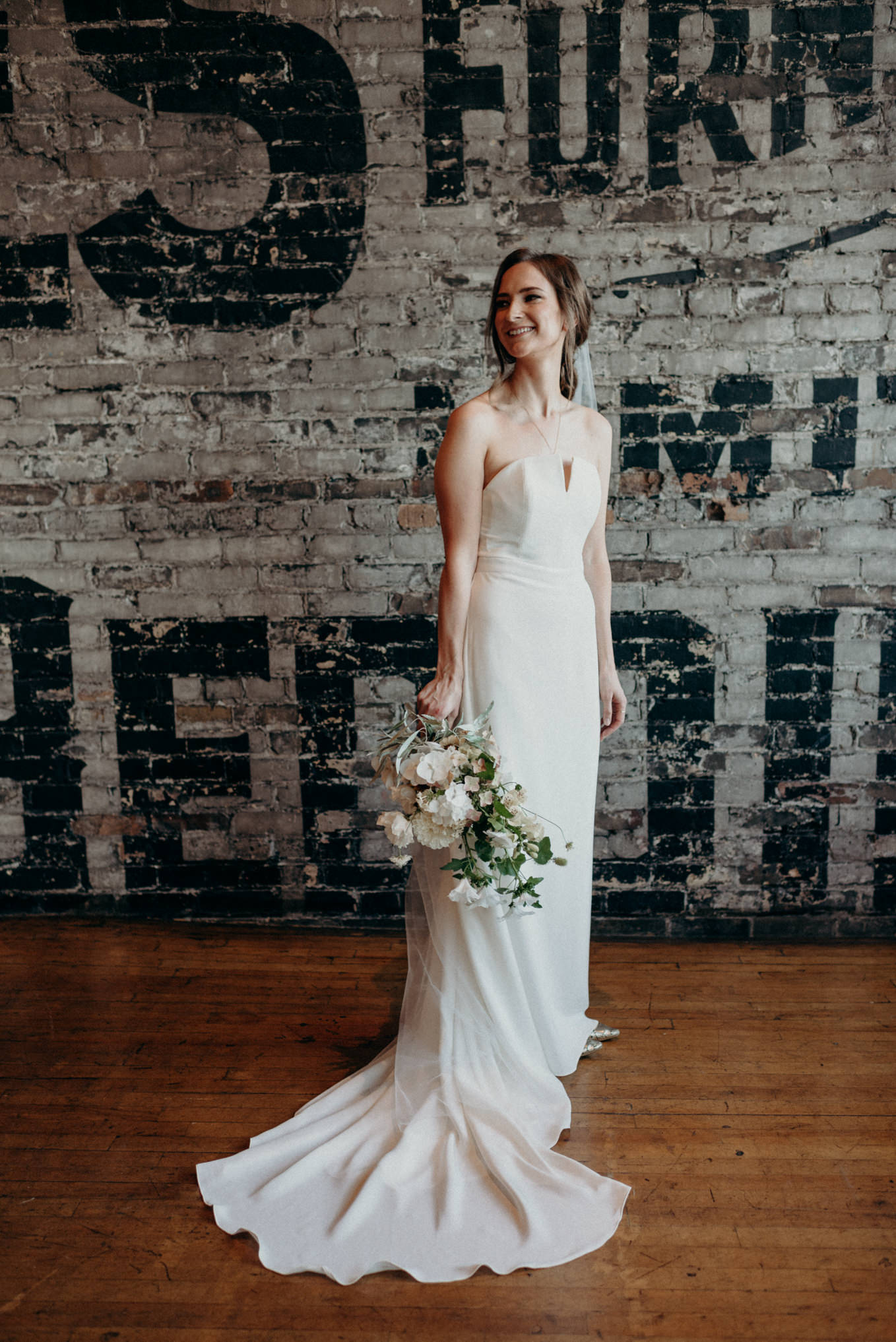 bride standing against brick wall at The Burroughes