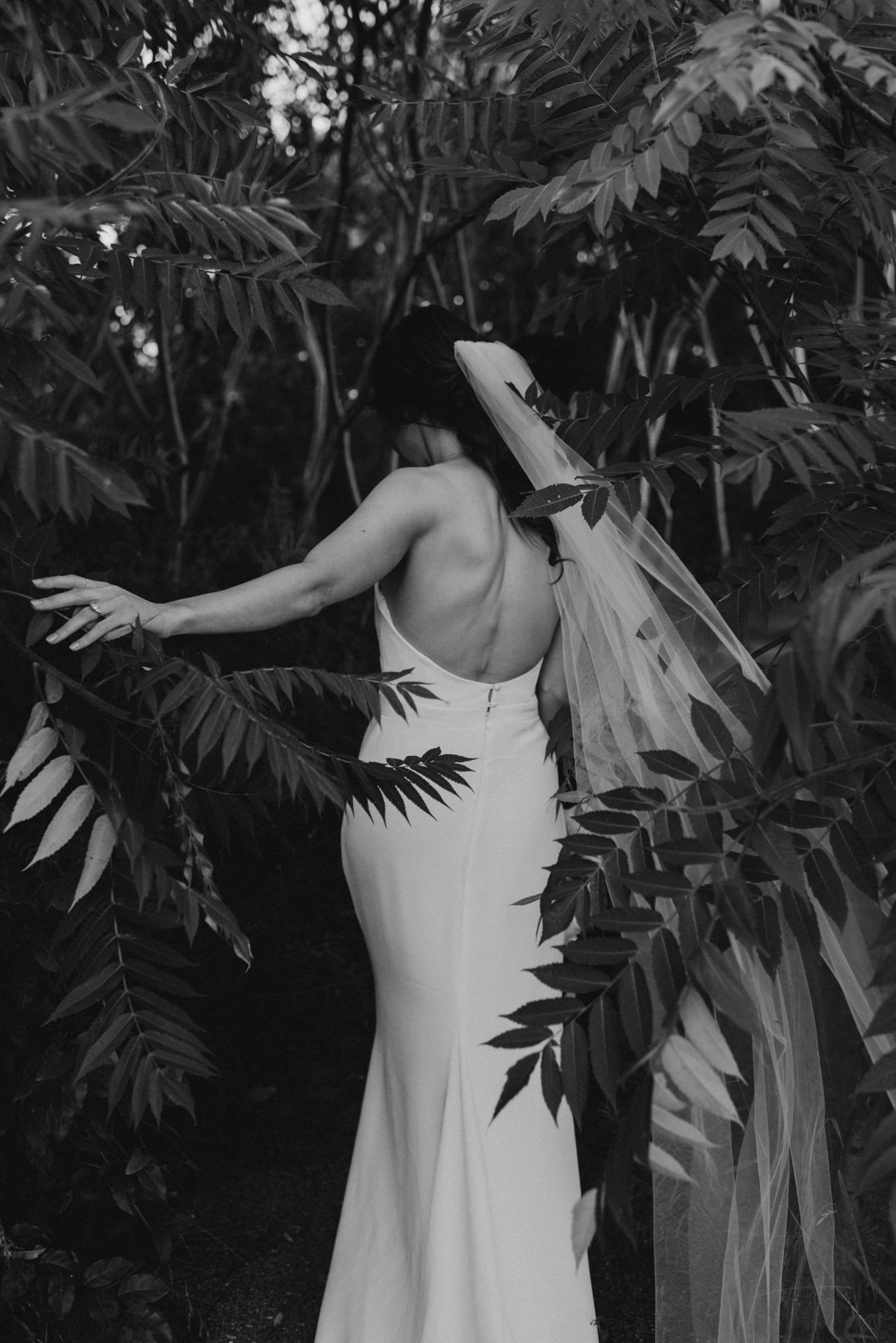 bride walking into sumac trees in black and white
