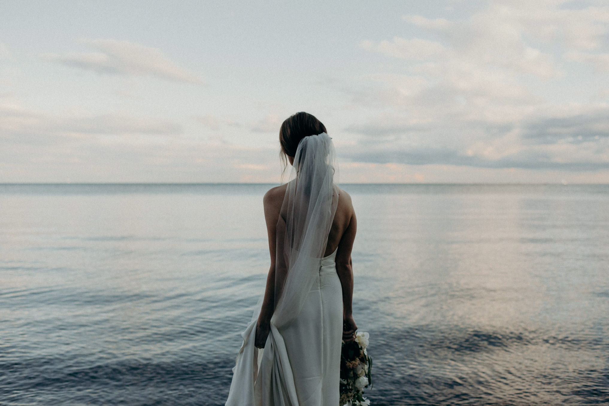 bride looking out onto calm lake Ontario at sunset in Toronto
