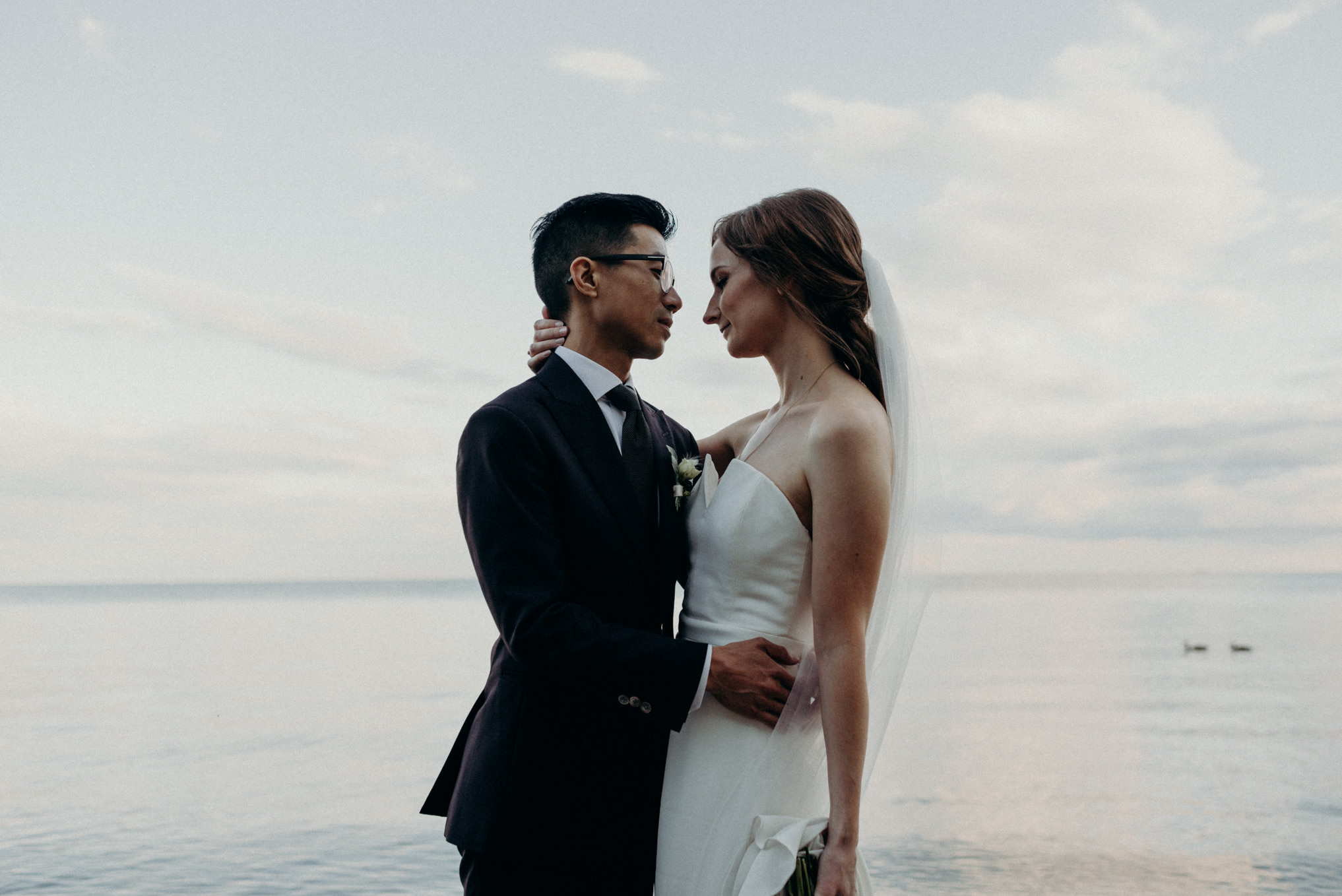 Bride and groom standing in front of calm lake Ontario, Humber Bay wedding portraits