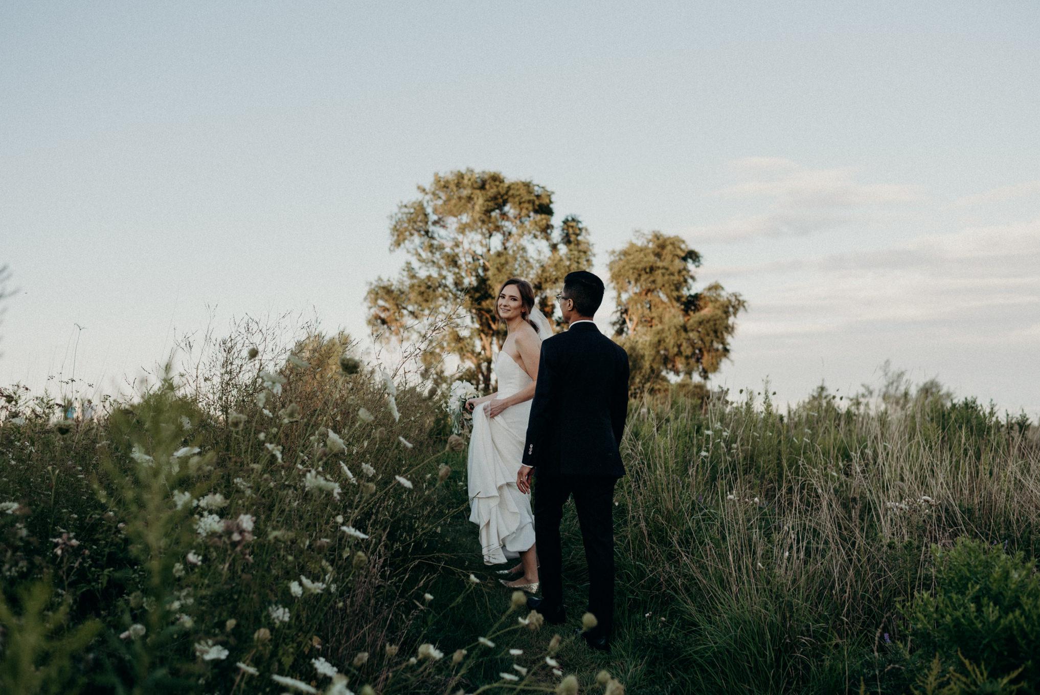 Bride and groom walking on path at Humber Bay