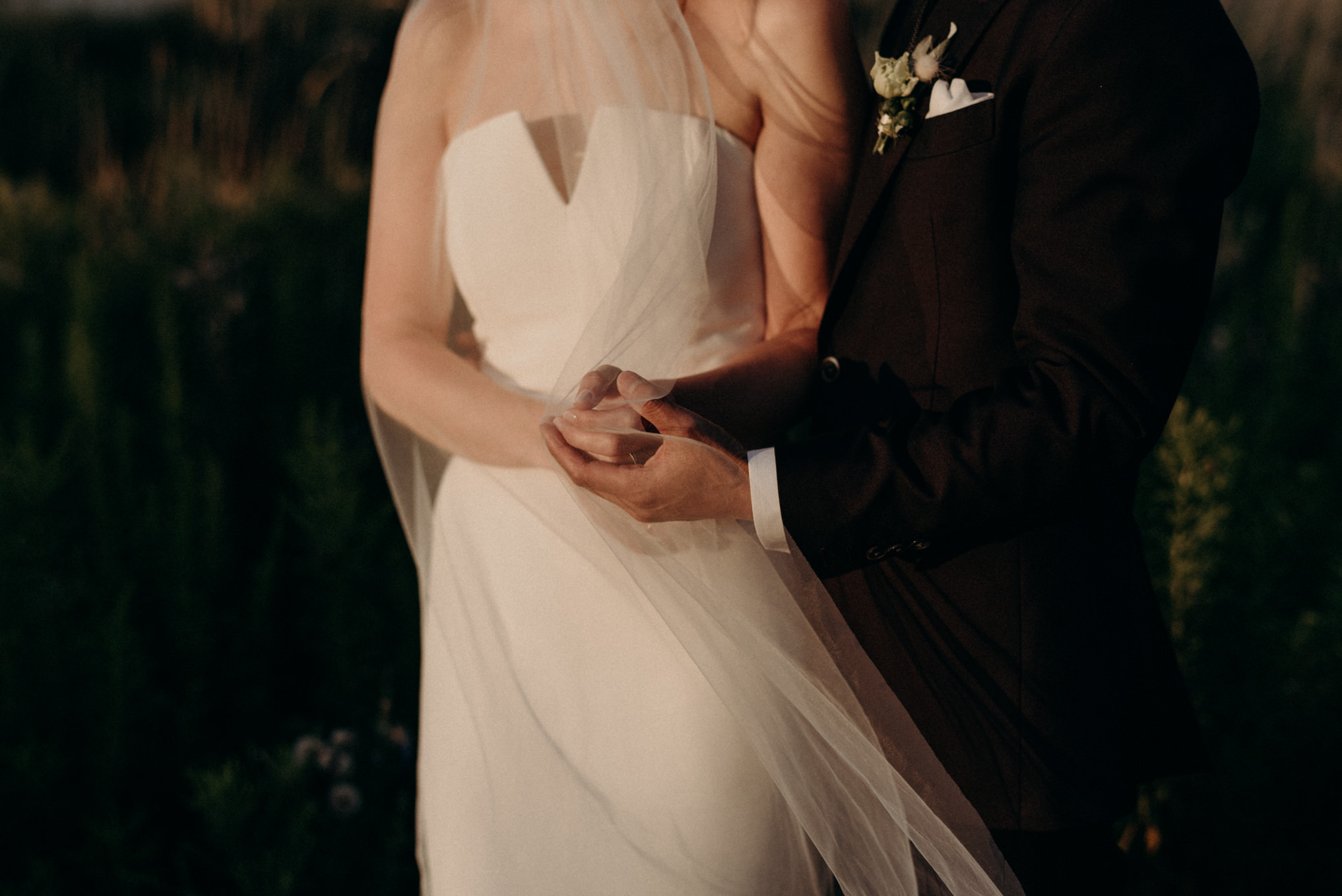 bride and groom standing in sunlight at sunset holding hands