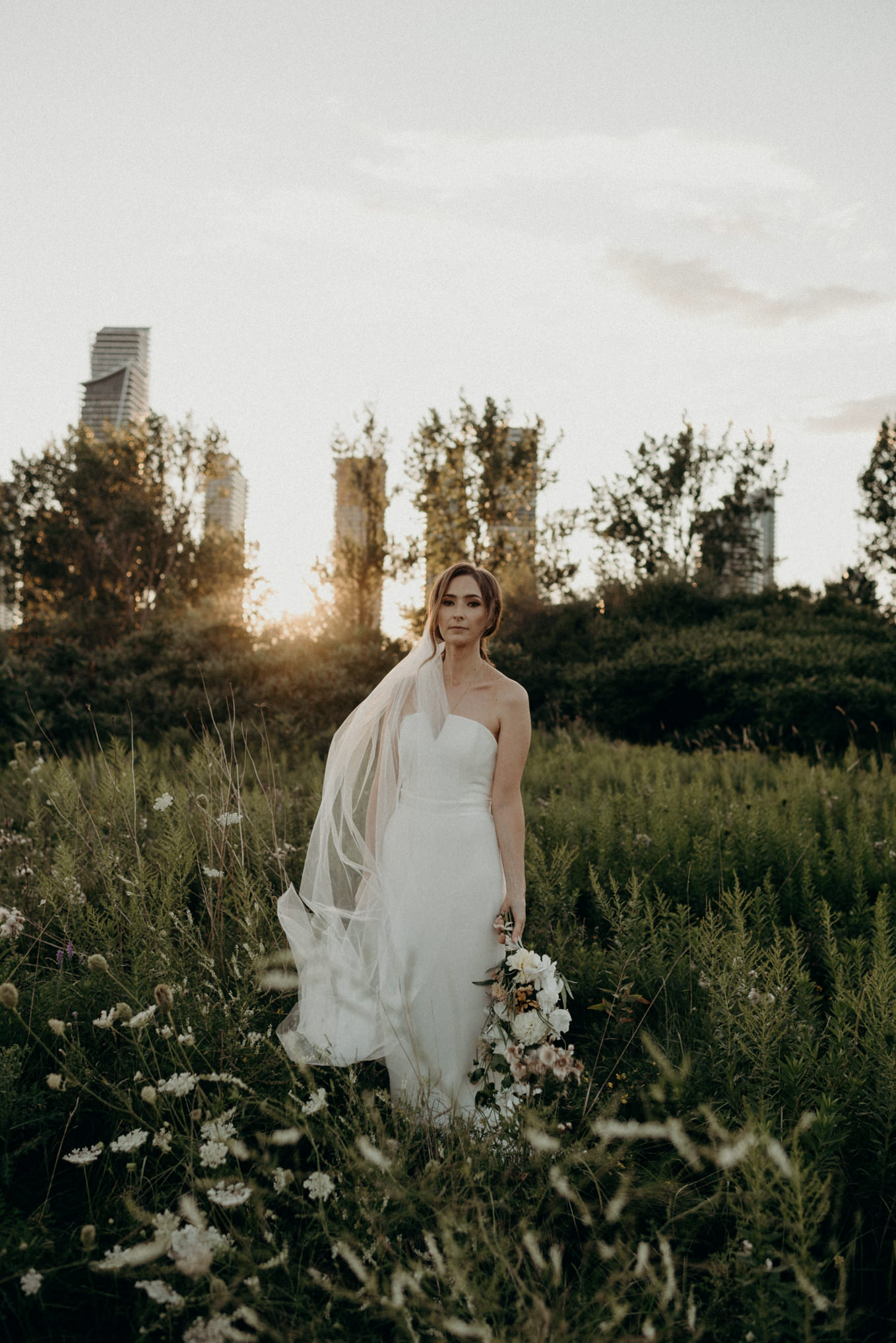 bride with sunset and condo buildings in background at Humber Bay. Toronto elopement portraits.