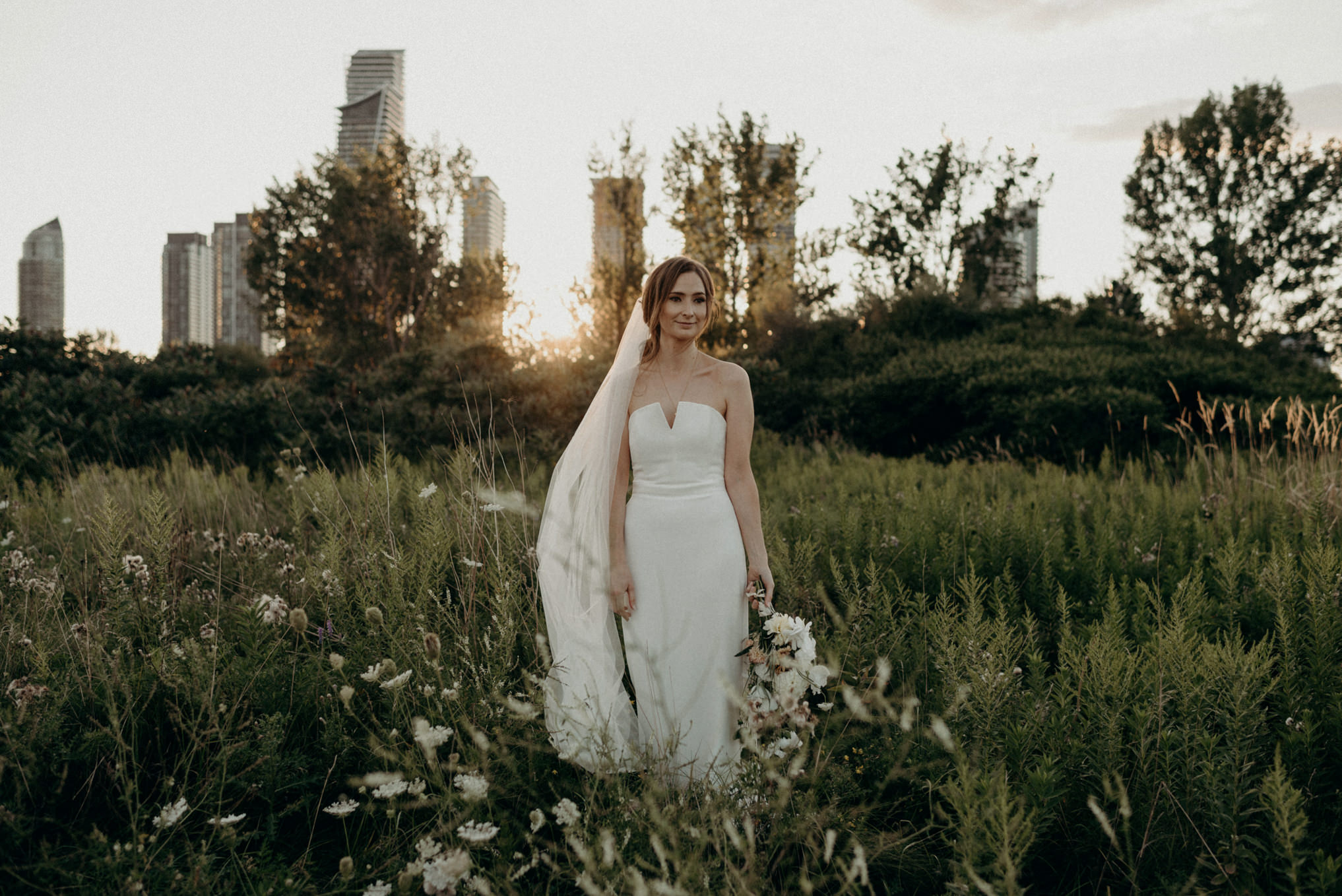 bride with sunset and condo buildings in background at Humber Bay