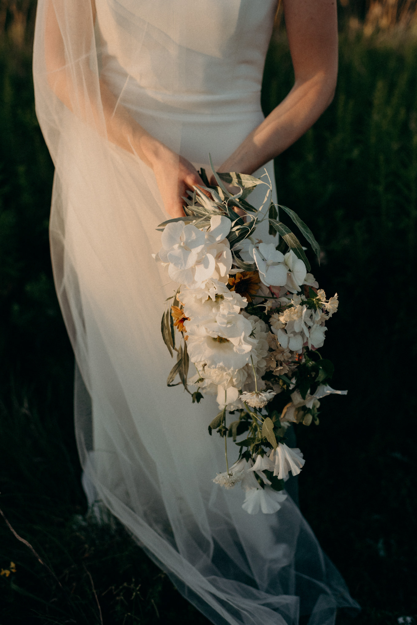 bride holding bouquet in sunlight from sunset