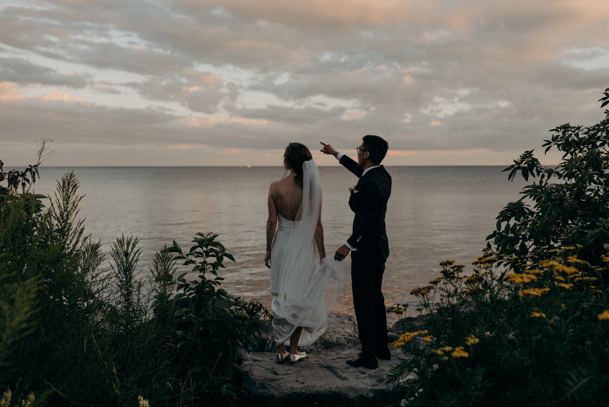 Bride and groom looking out onto Lake Ontario at sunset. Humber Bay elopement in Toronto
