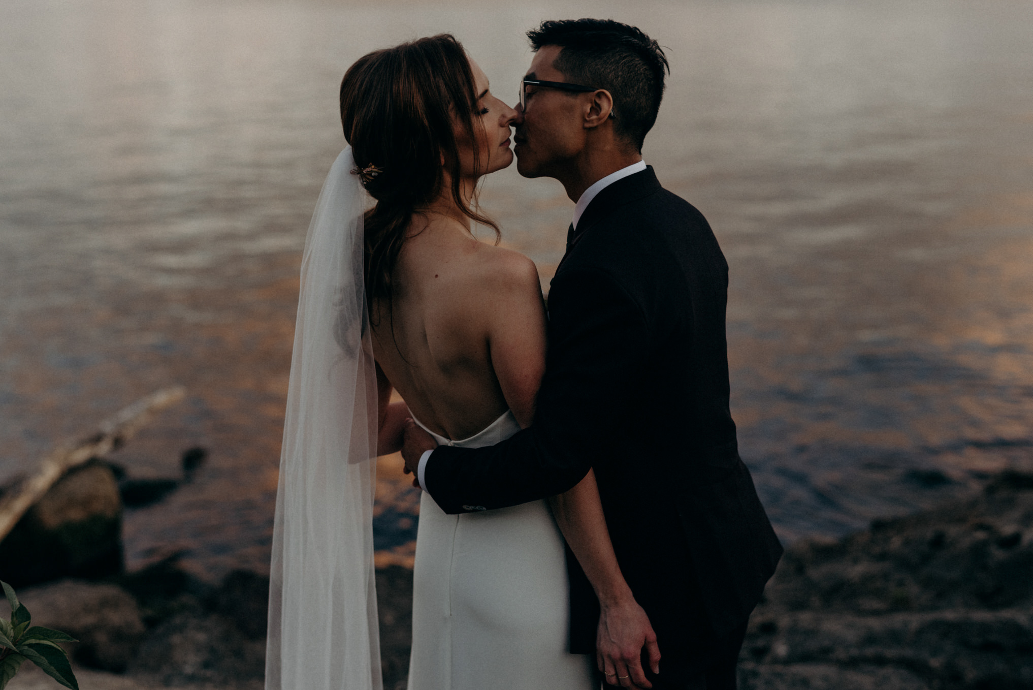 Humber Bay wedding portraits. Bride and groom kissing with sunset reflecting off water behind them
