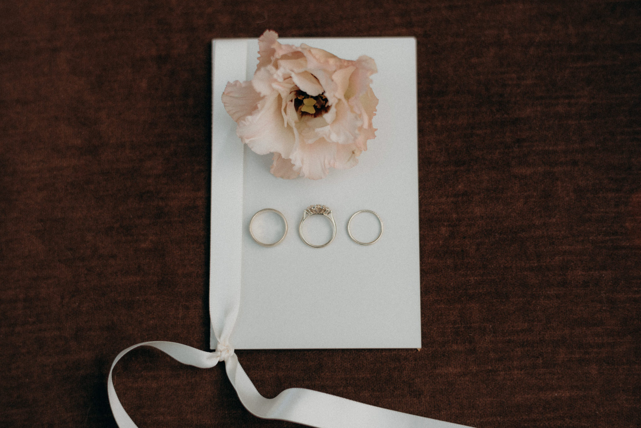 wedding rings and flower on vow book