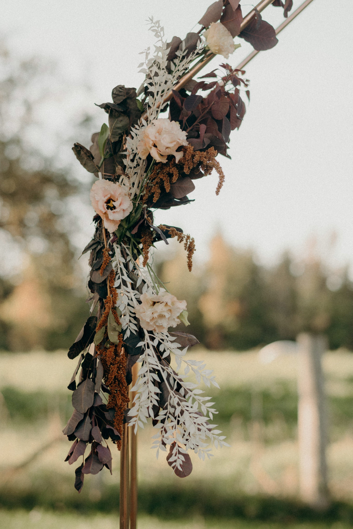 flowers on copper ceremony arch backdrop