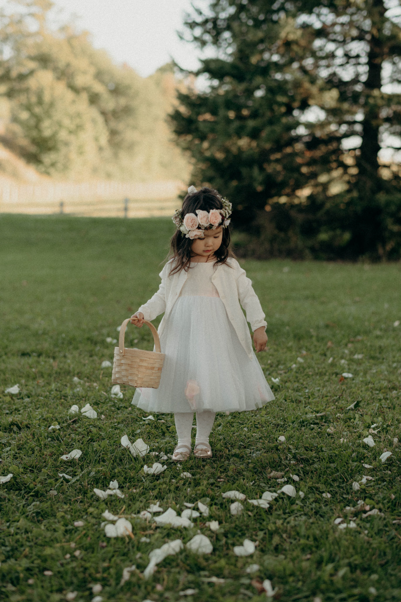 flower girl in floral crown throwing rose pedals down grass aisle