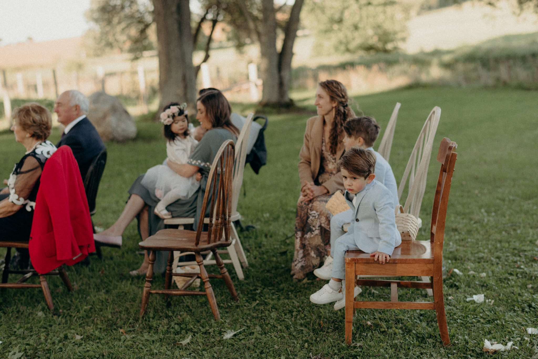 guests on mismatched chairs during outdoor wedding ceremony