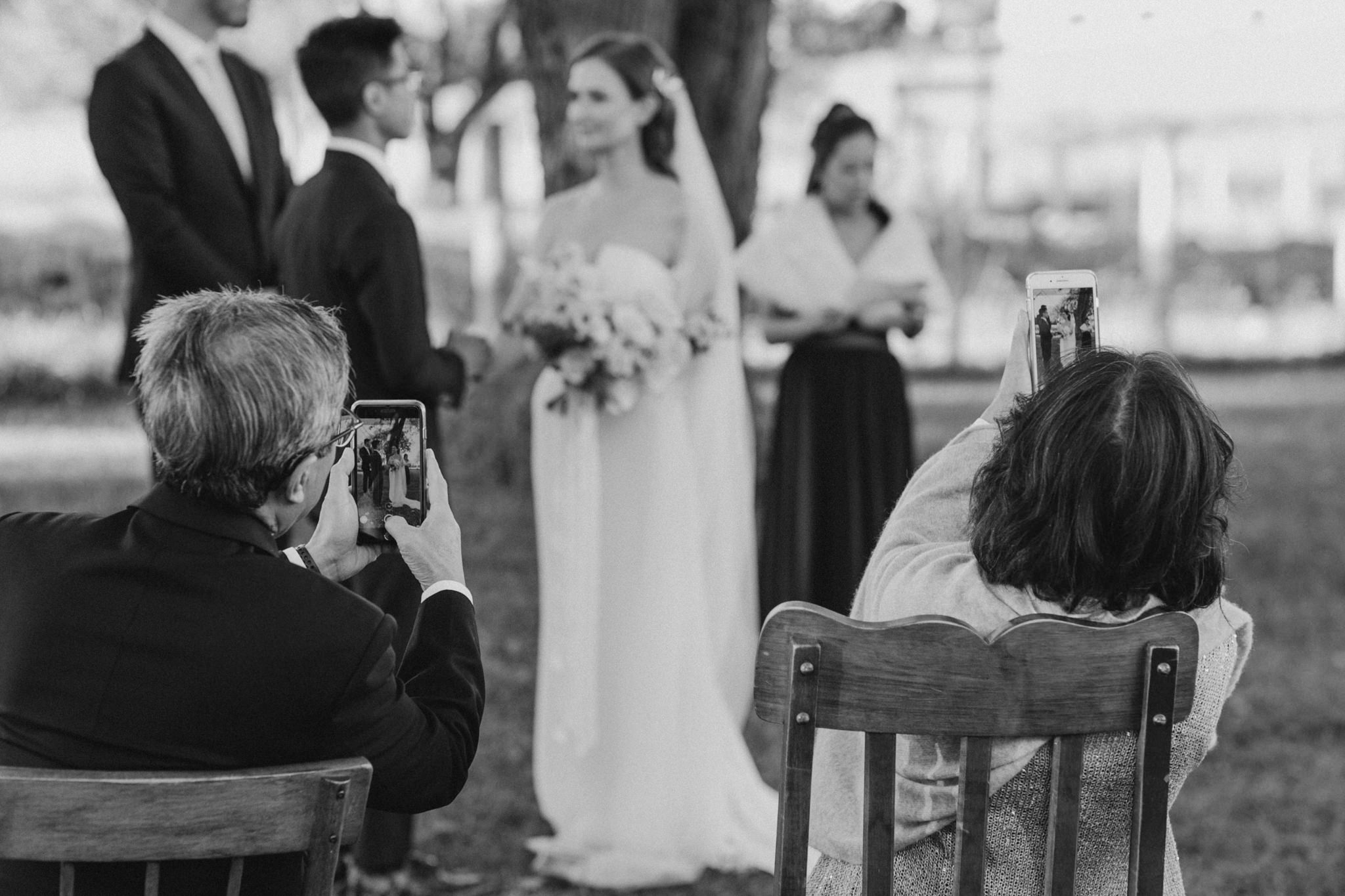 guests taking pictures with cellphones at wedding