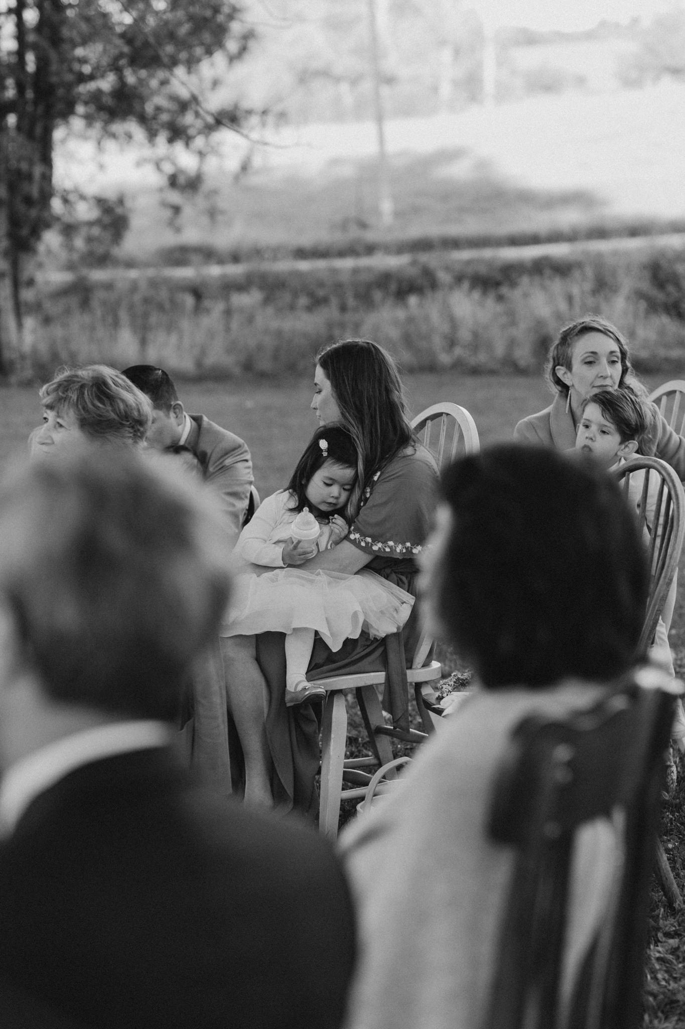 little girl asleep on mothers lap at wedding