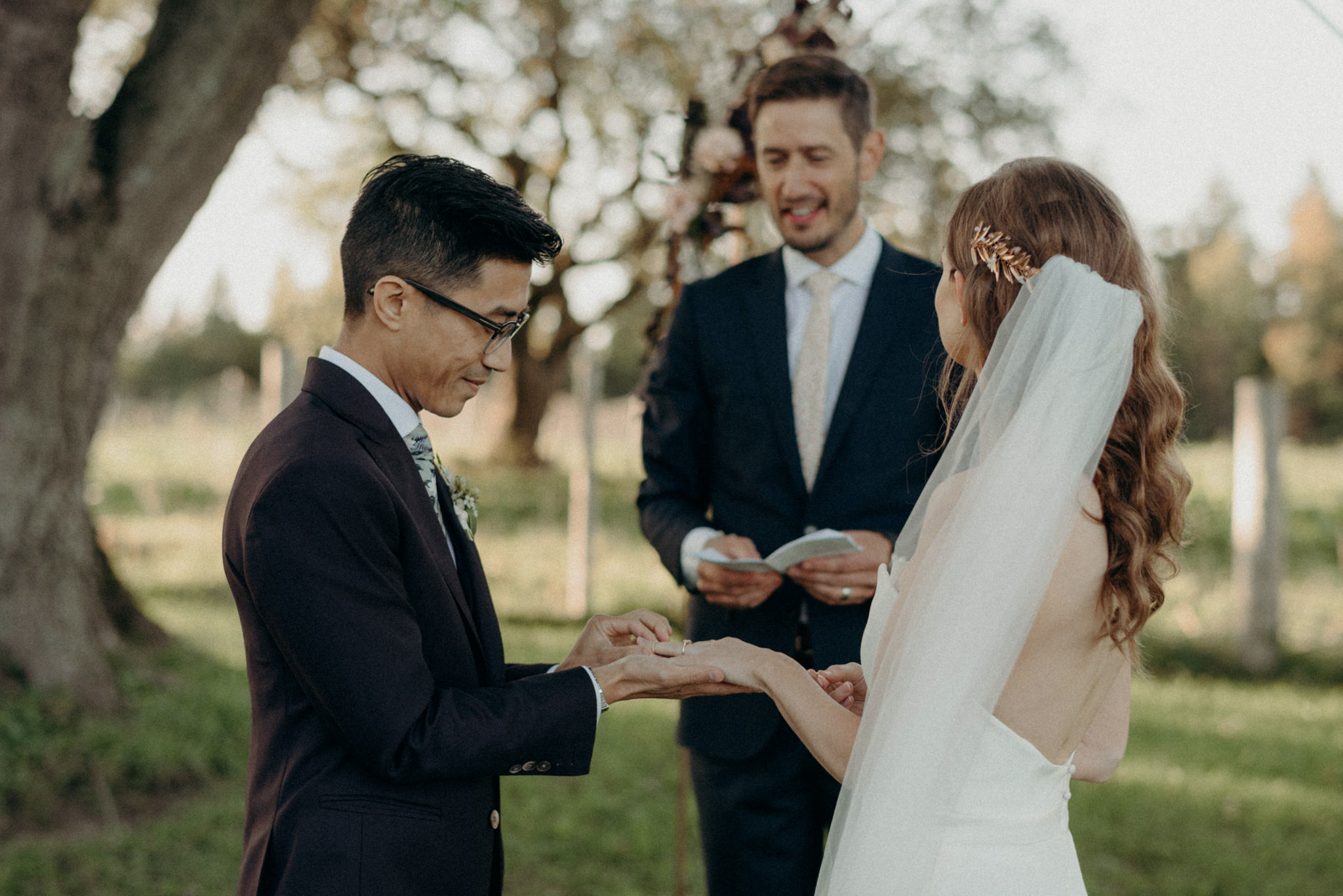 couple exchanging rings during outdoor wedding ceremony