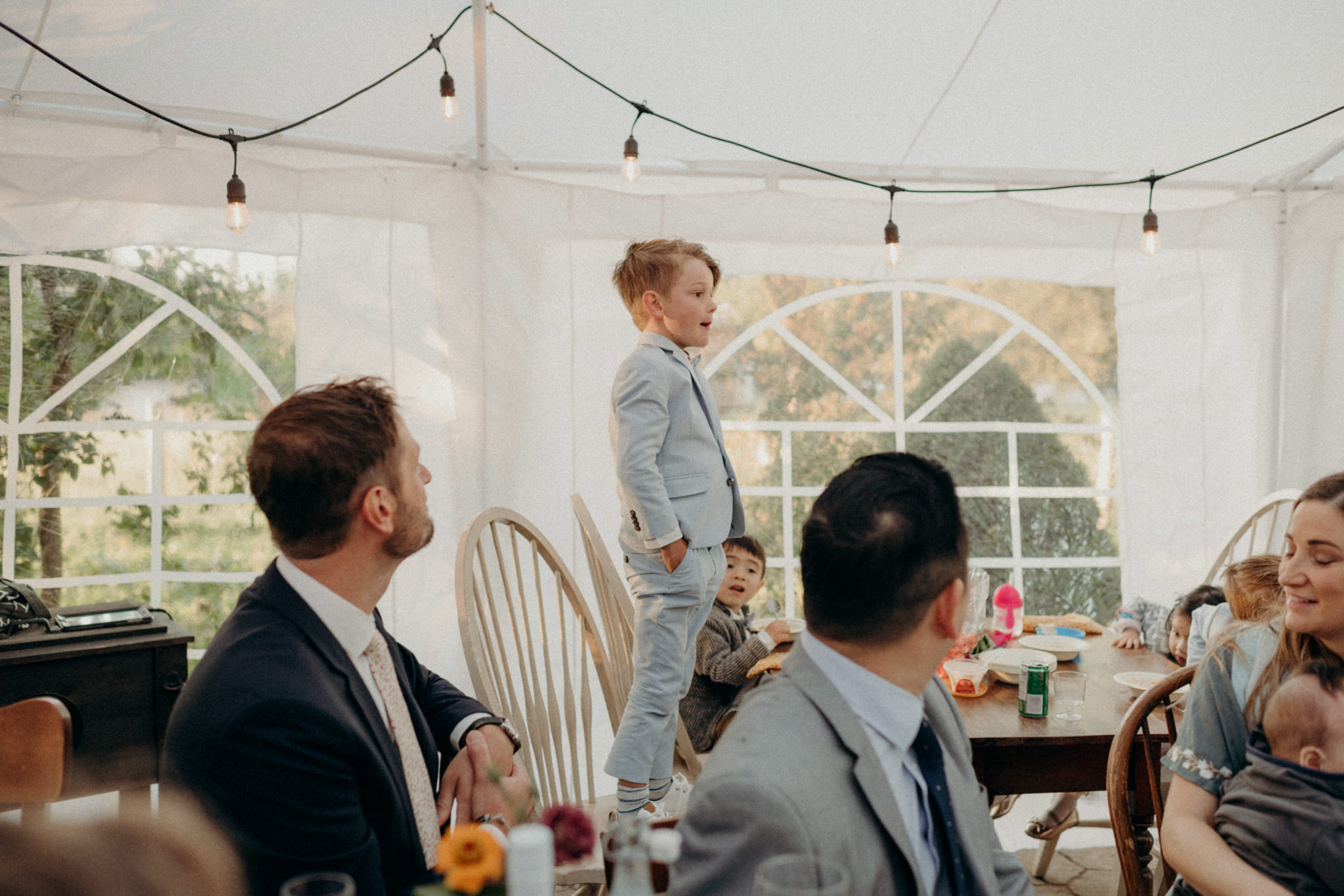 little boy standing on chair saying irish blessing before dinner. intimate tent wedding reception at Good Family Farms
