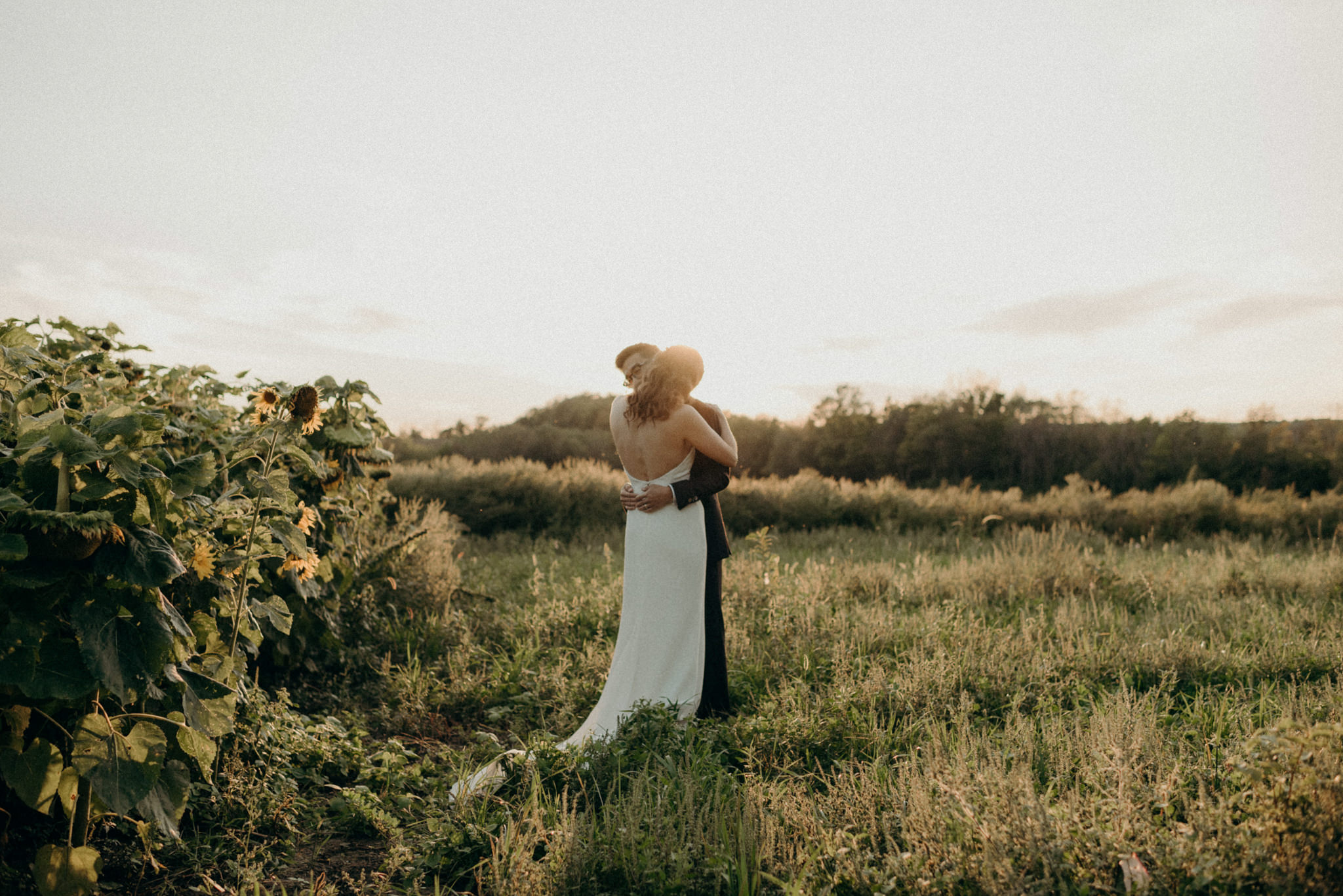 Couple hugging in a field at sunset. Good Family Farms wedding.