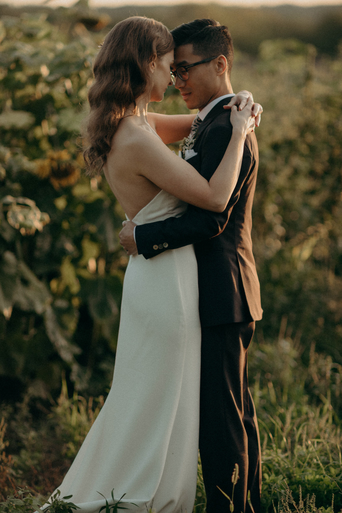 Wedding portraits by sunflowers at sunset