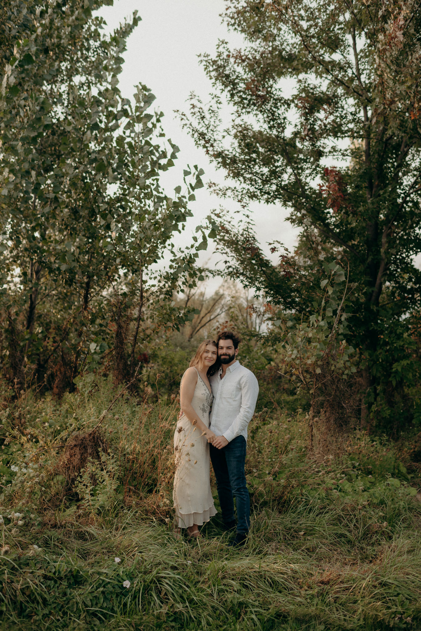 Couple smiling at camera in a field with trees