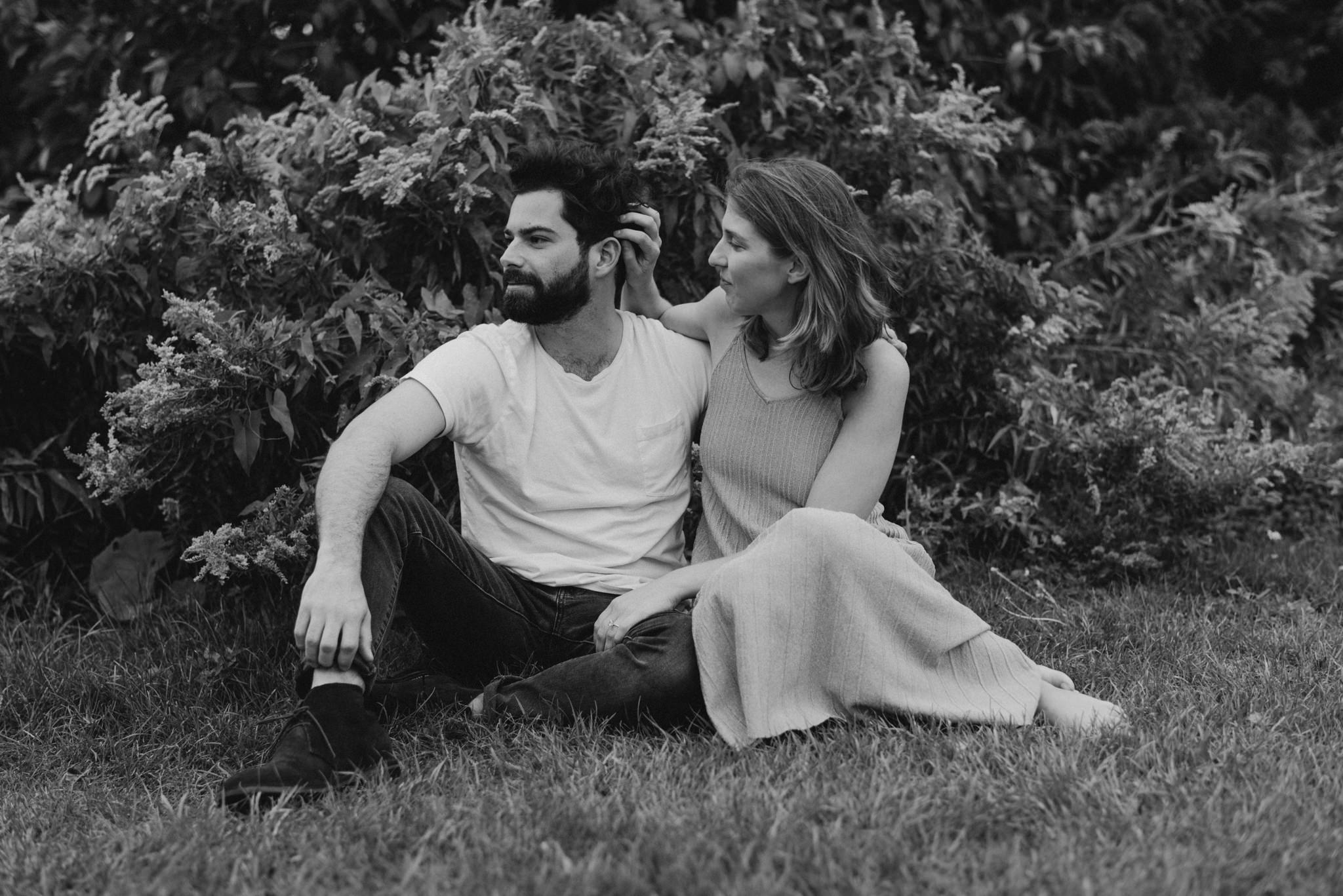 romantic black and white photo of couple sitting on grass hugging