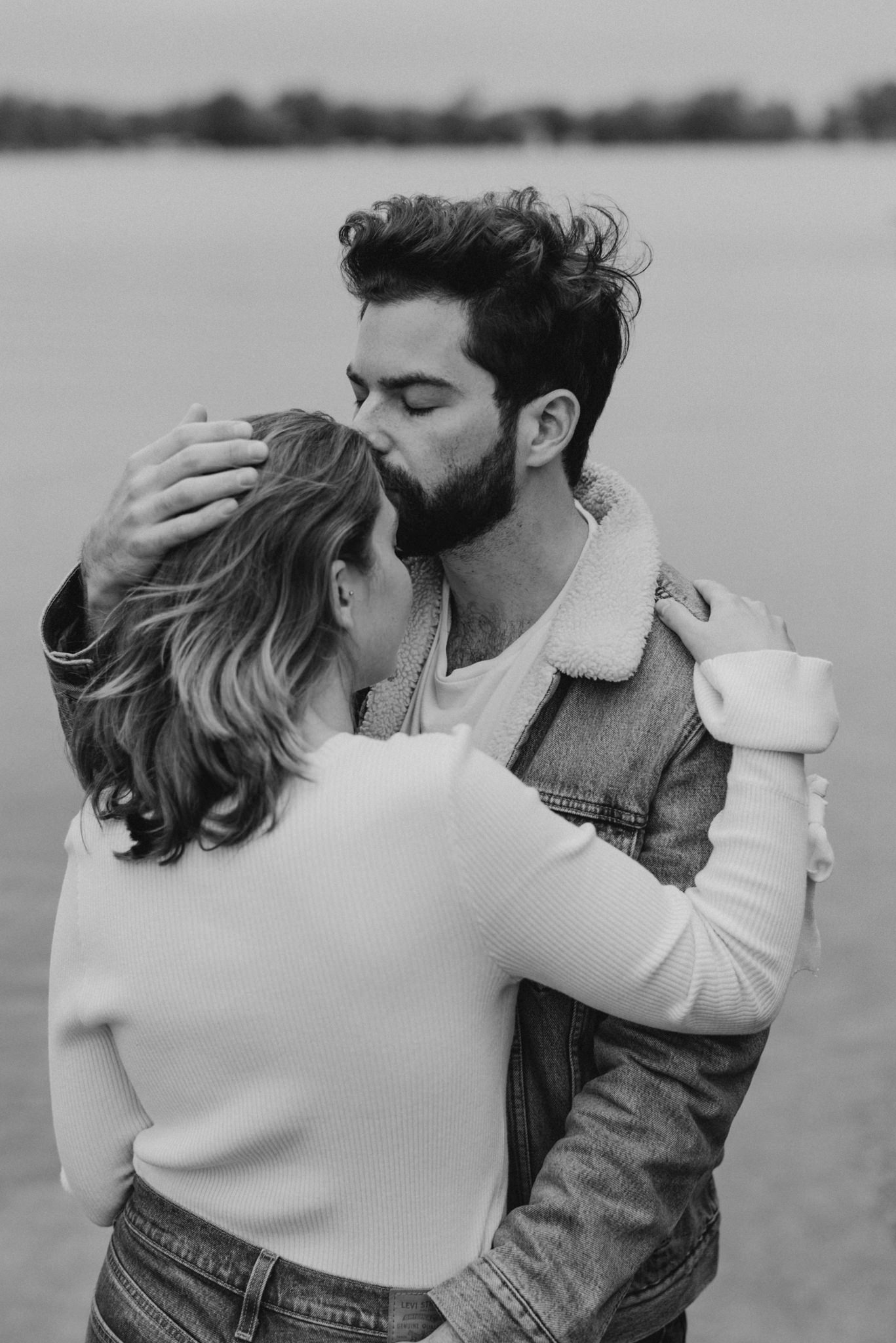 Guy kissing woman on the forehead. Black and white portrait.
