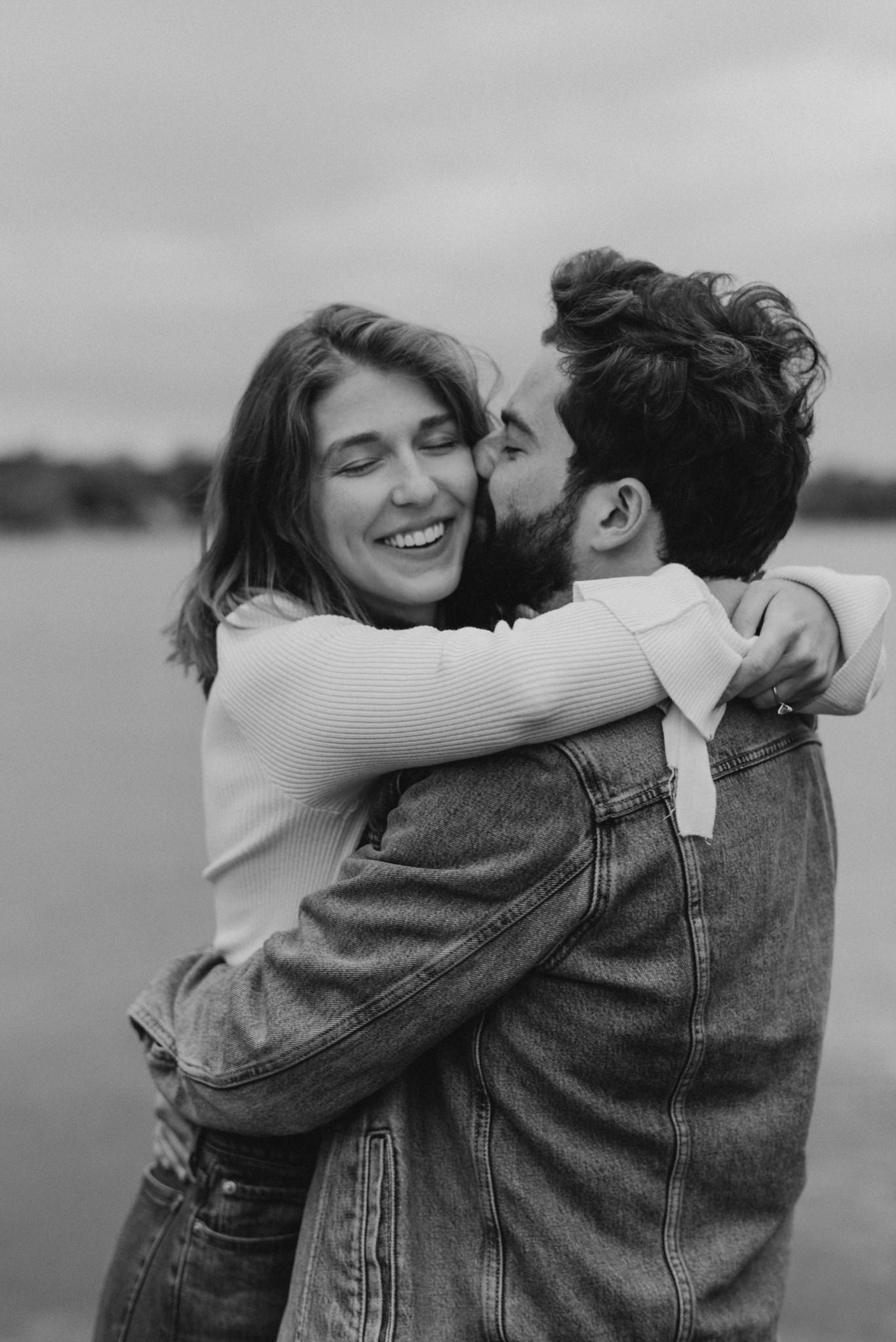 romantic black and white portrait of guy kissing woman on the cheek by the water in Levi's jeans
