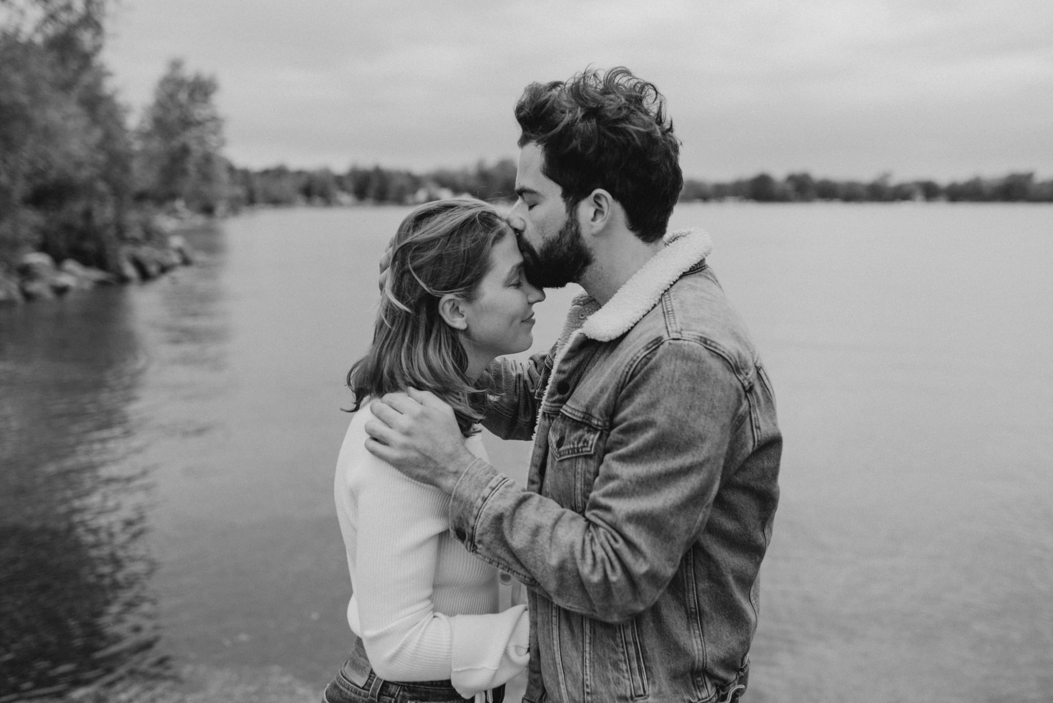 black and white portrait of guy kissing woman's forehead