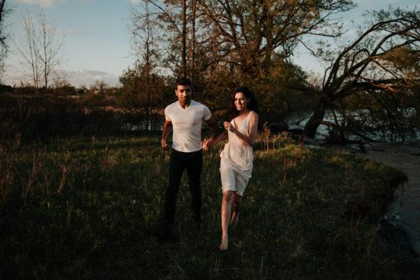 Dreamy wanderlust couple running barefoot in open field towards camera at sunset