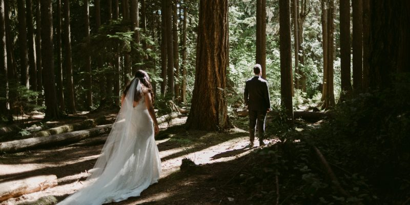 Bride walking towards groom for first look in forest