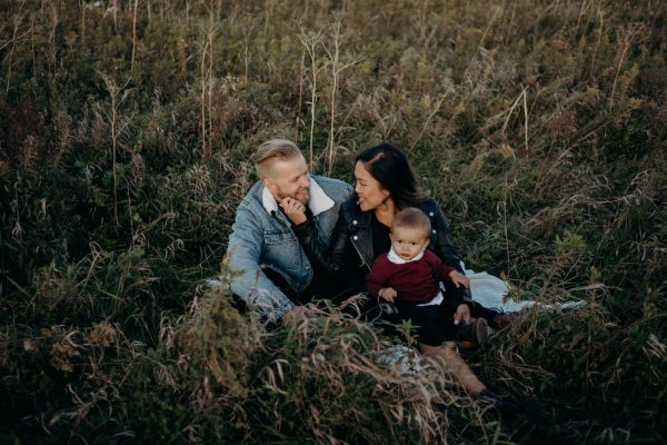 Young couple sitting in tall grass with baby boy
